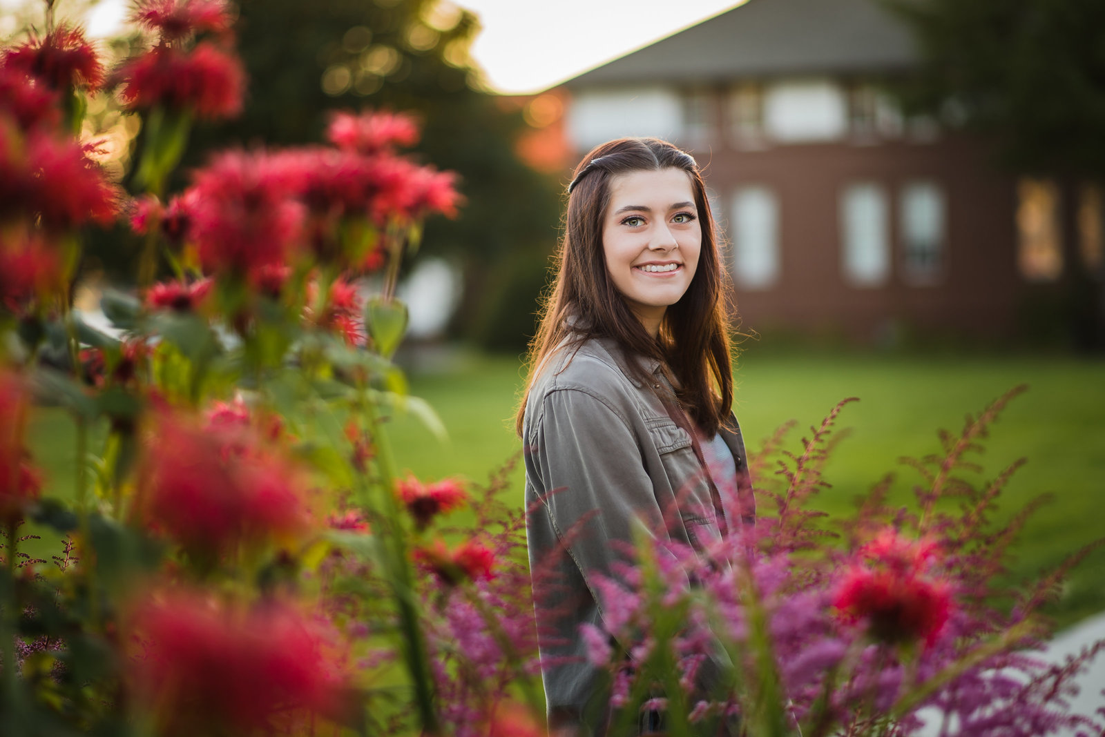 A high school senior girl posing in front of beautiful flowers on the sheldon jackson campus in sitka alaska