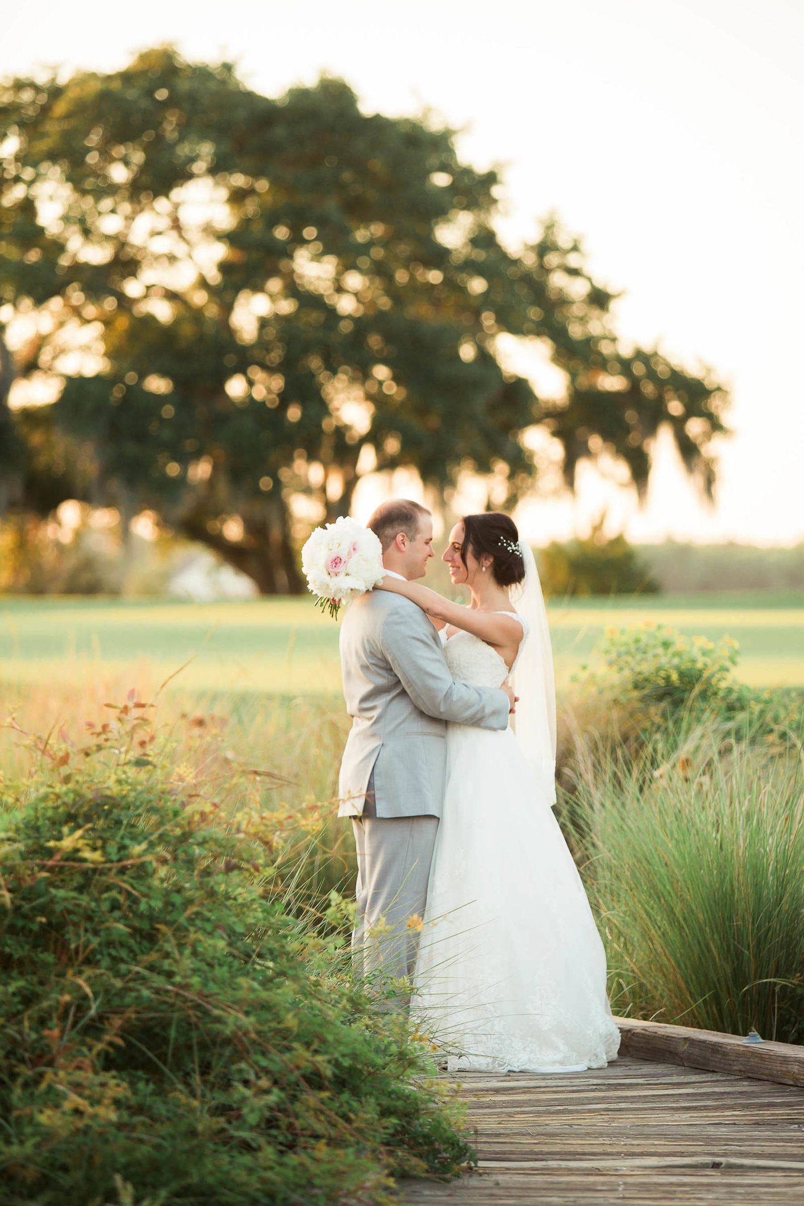 Bride and groom stand in a field at sunset, Daniel Island Club, Charleston, South Carolina