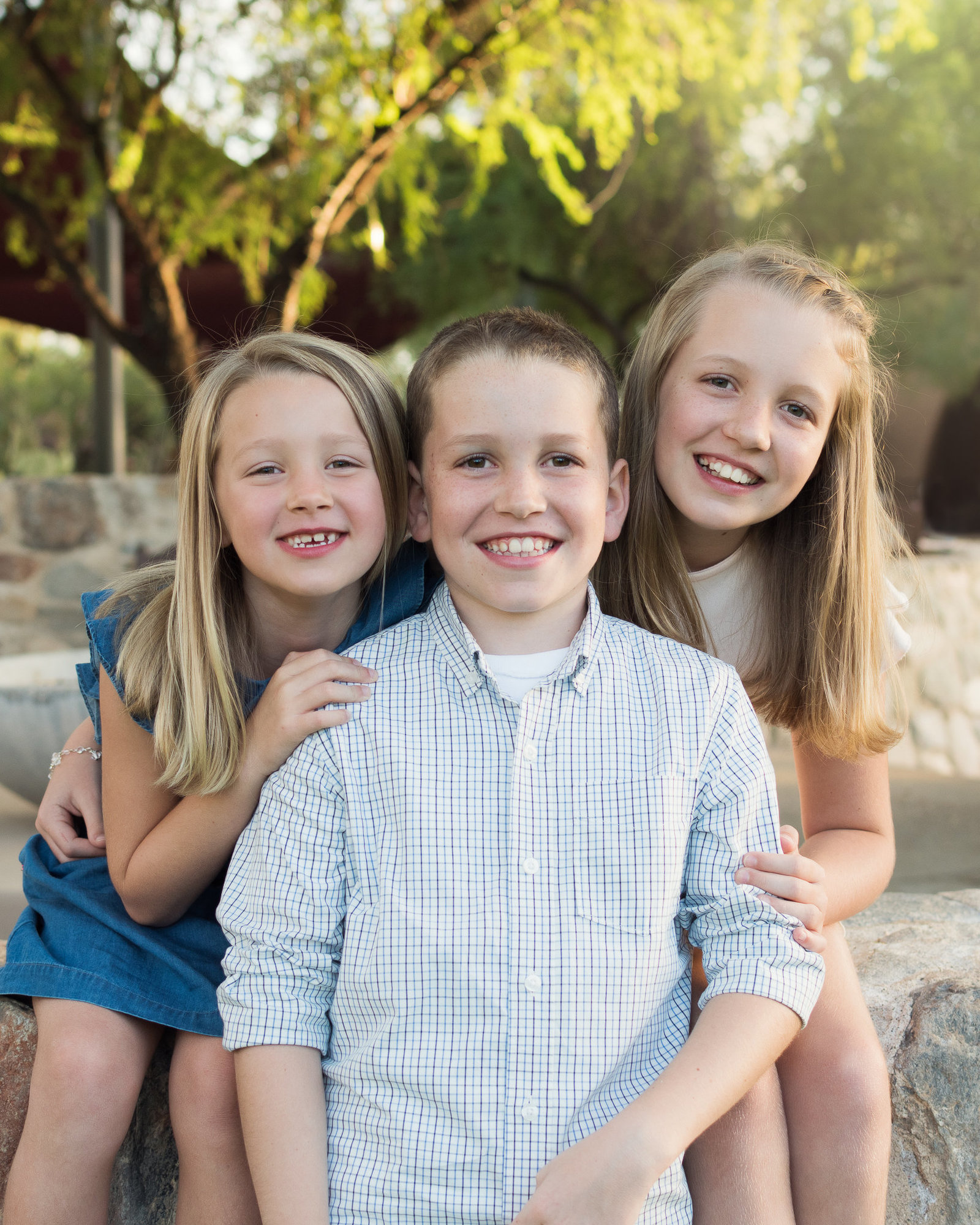 three children snuggling close to each other sitting on a stone wall