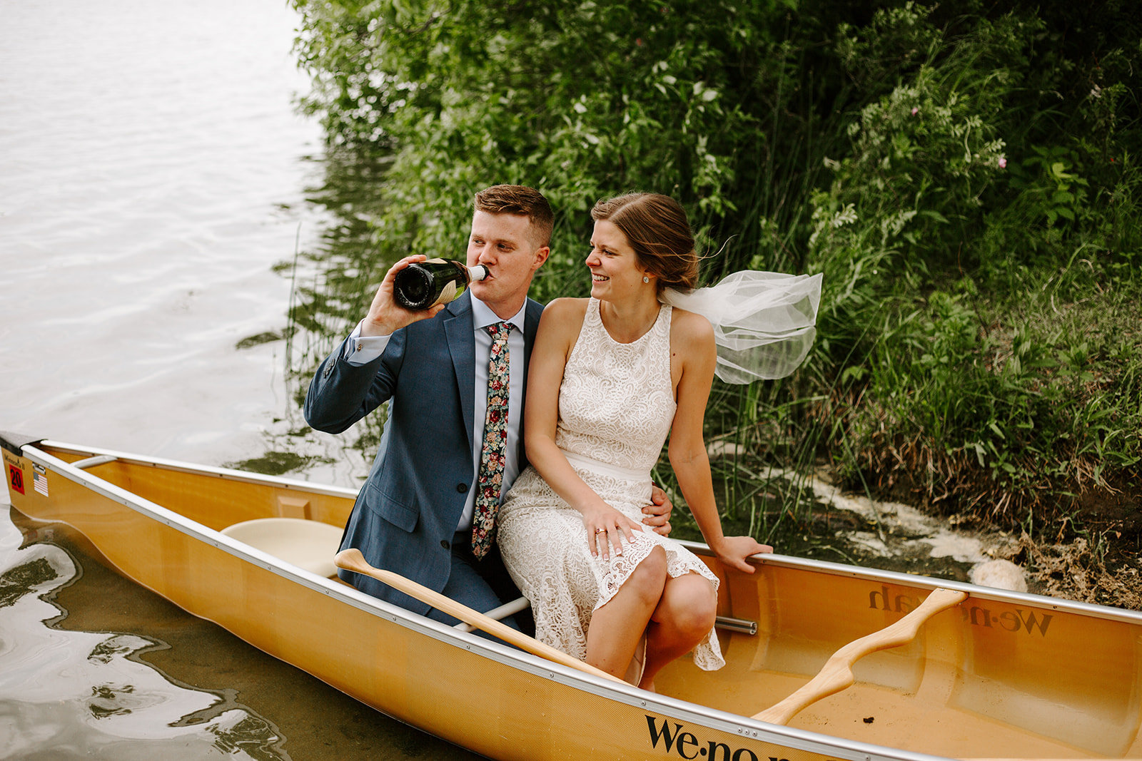 A couple drinking champagne in a canoe during their wedding elopement
