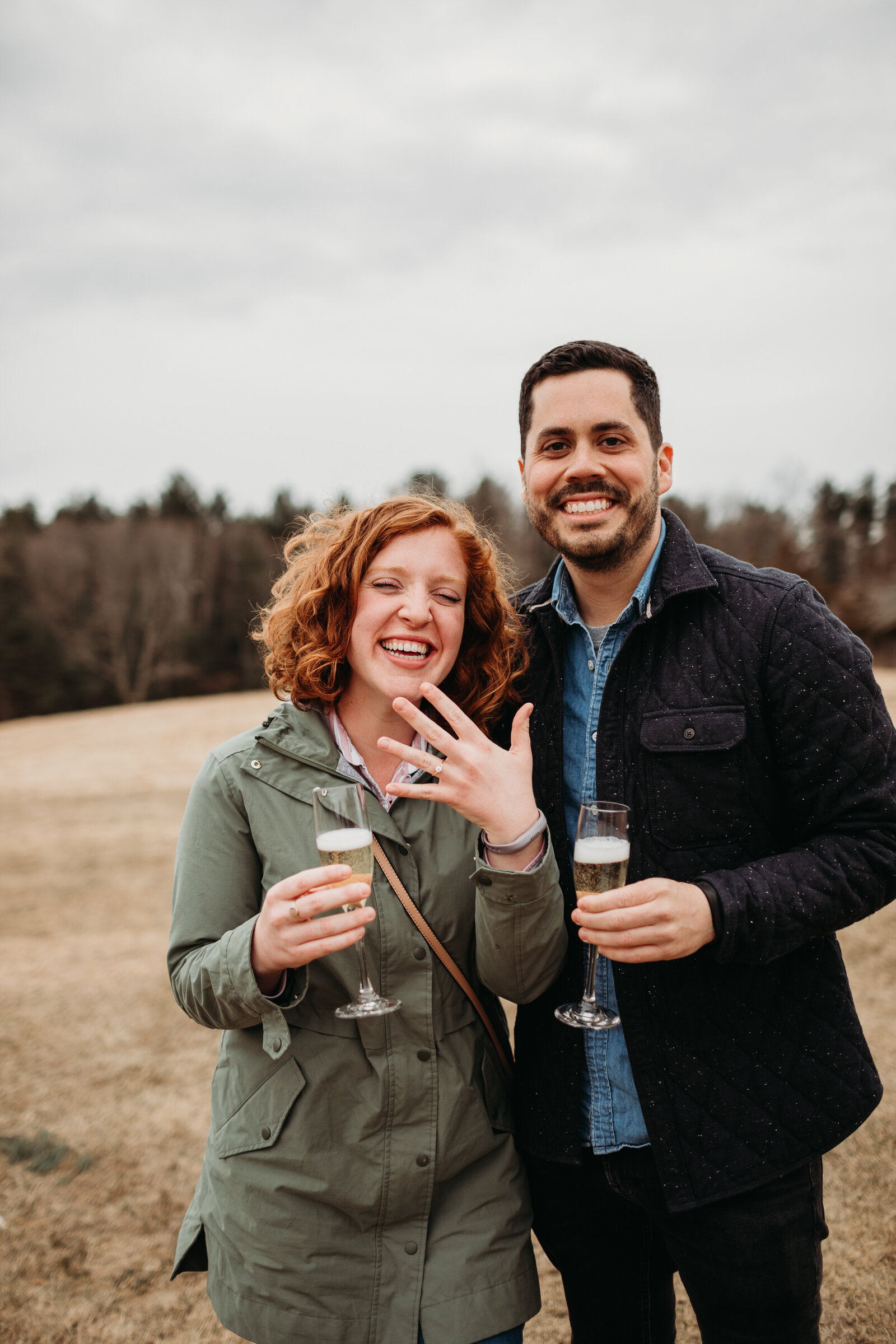 couple laughs as they show their engagement ring