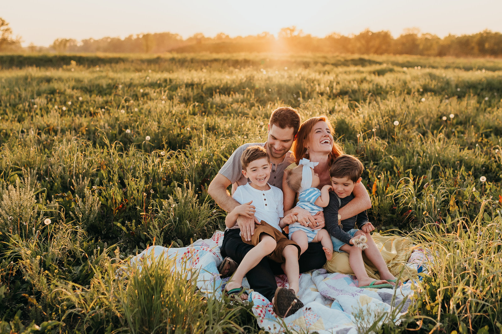 family siting on a blanket laughing in a field at sunset