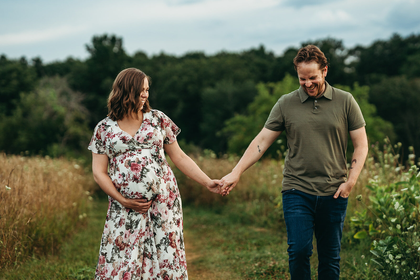pregnant couple holds hands and laughs while walking