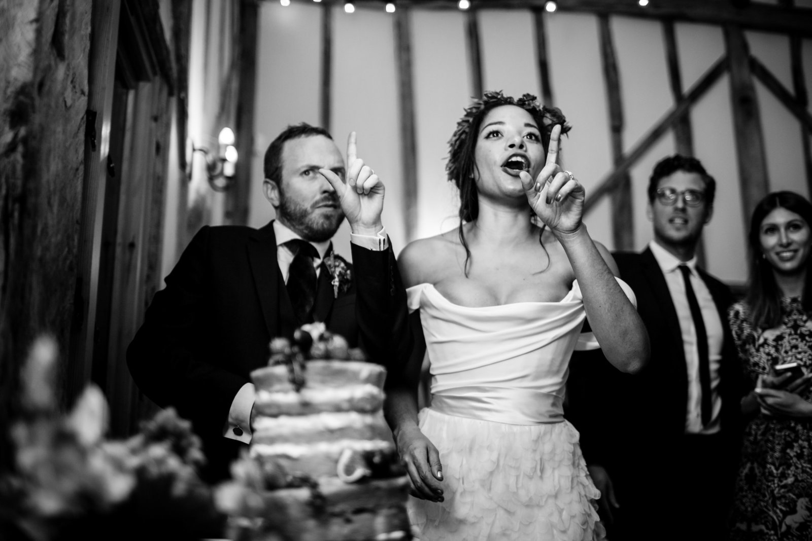 Bride and Groom cut their wedding cake whilst making the 'loser' sign at a guest and smiling in a Norfolk barn wedding venue.