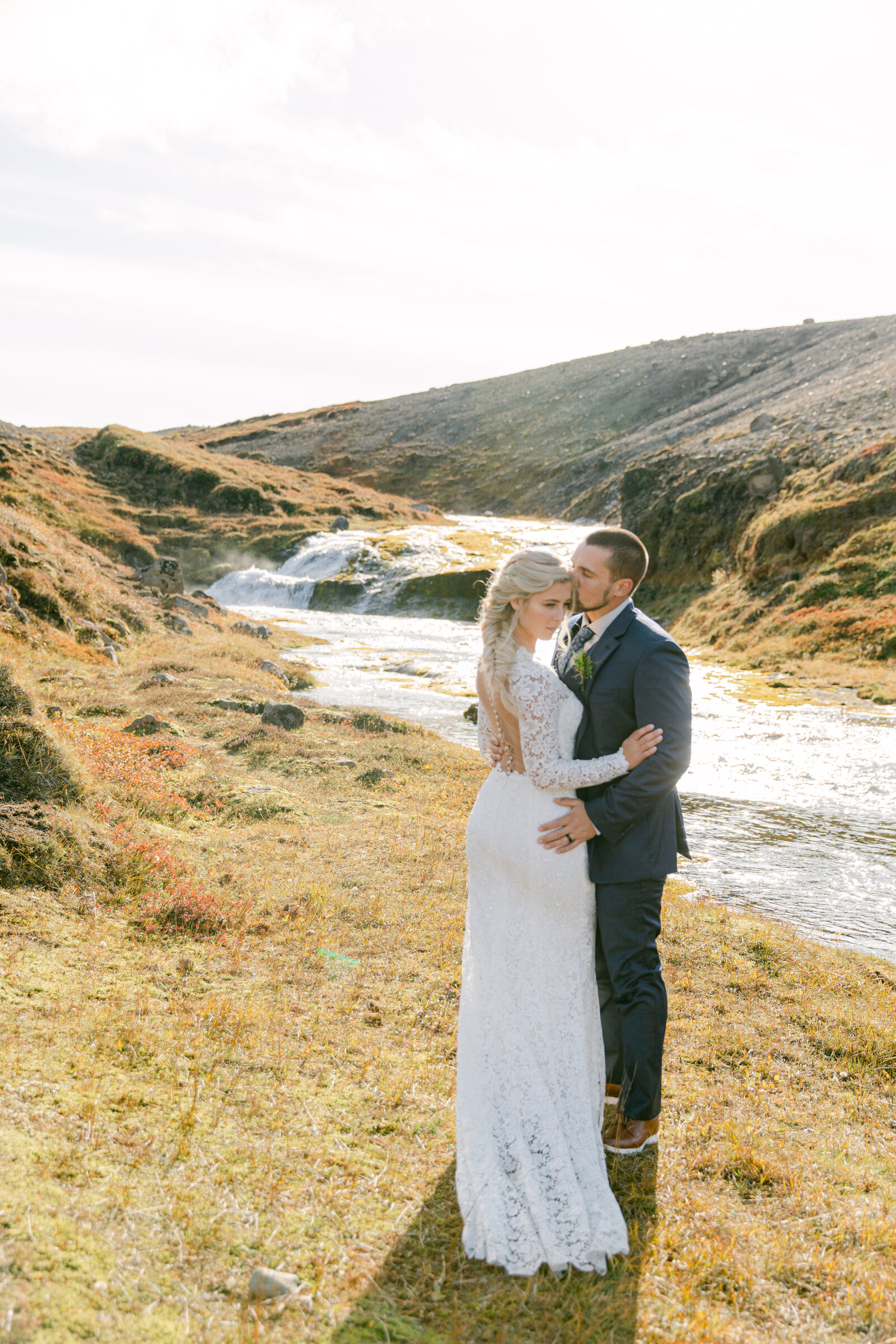 bride and groom face each other in iceland terrain near a waterfall