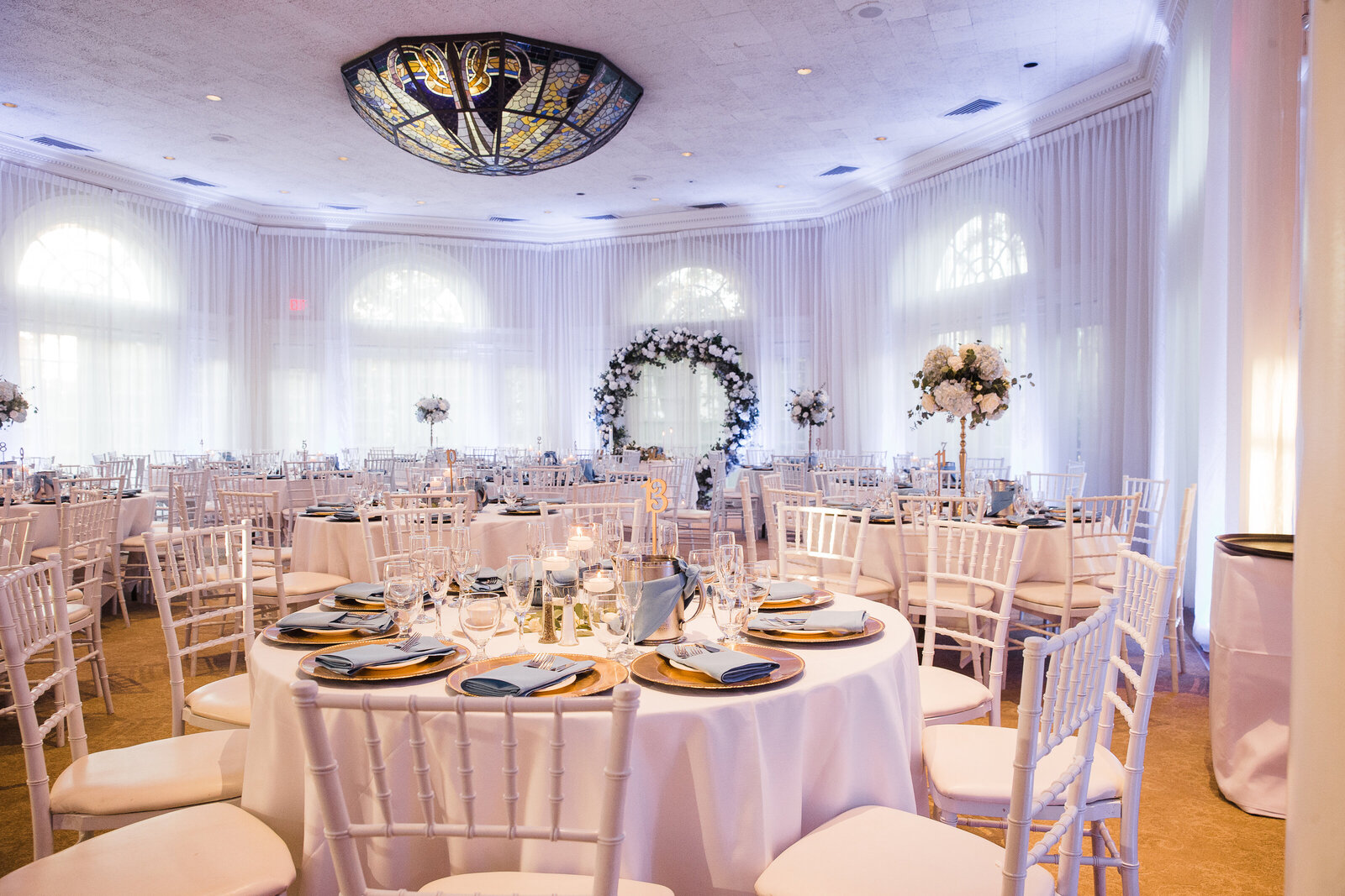 Surrounded by soft draping, the reception guest tables are captured moments before the reception begins.