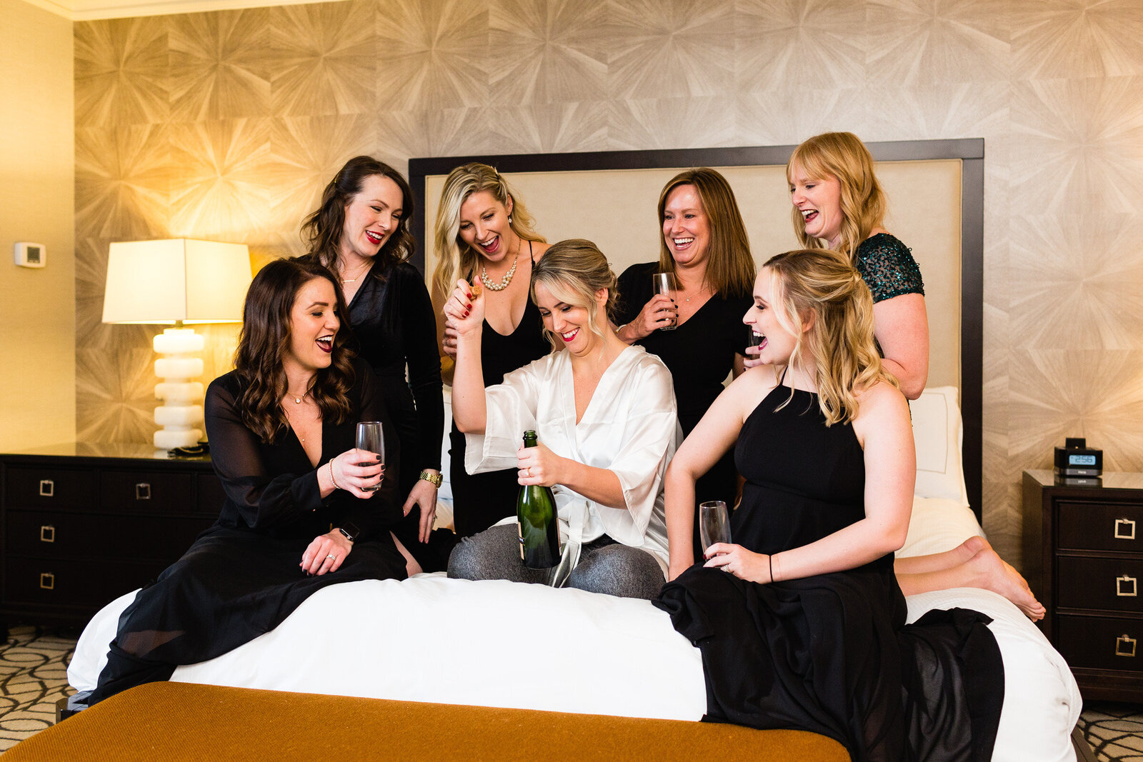bridal party pops champagne on hotel bed ohio