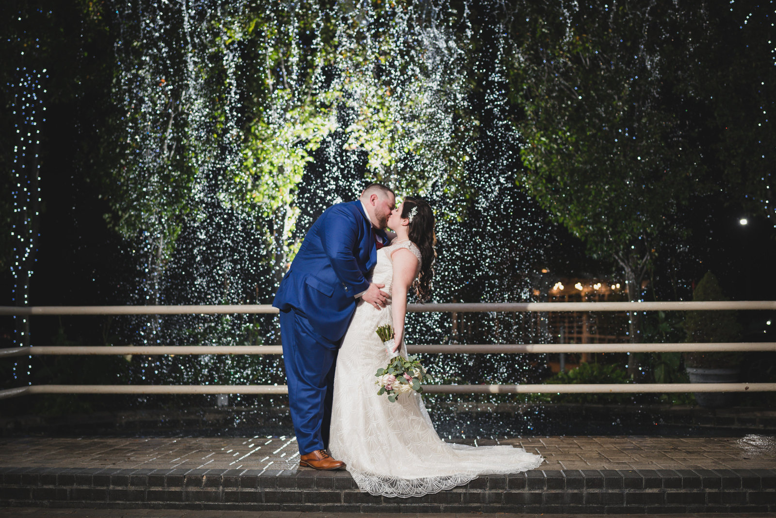 bride and groom kiss by fountain at Chateau Briand