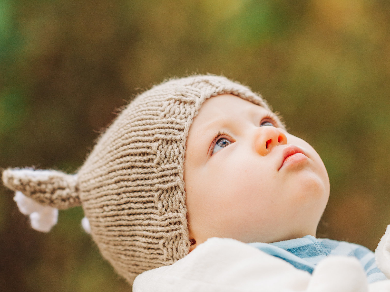 Baby with blue eyes in a knit cap looks up at the sky