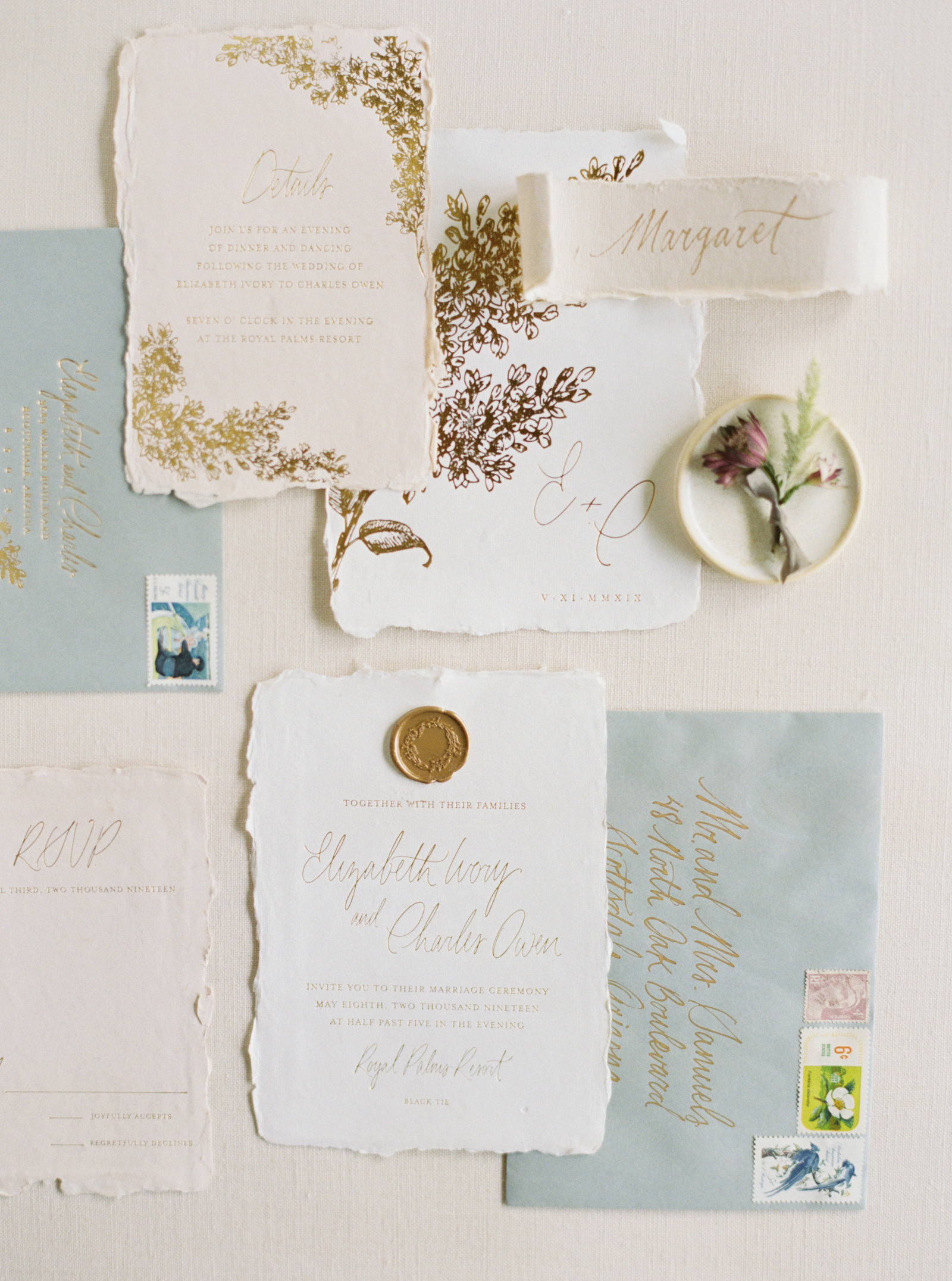 Fine art wedding invitation with calligraphy, handmade paper, and vintage stamps