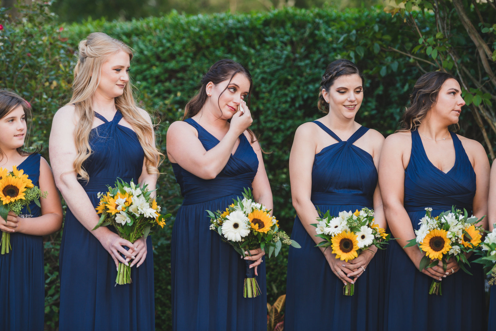 photo of emotional bridesmaids holding their bouquets from wedding at Three Village Inn