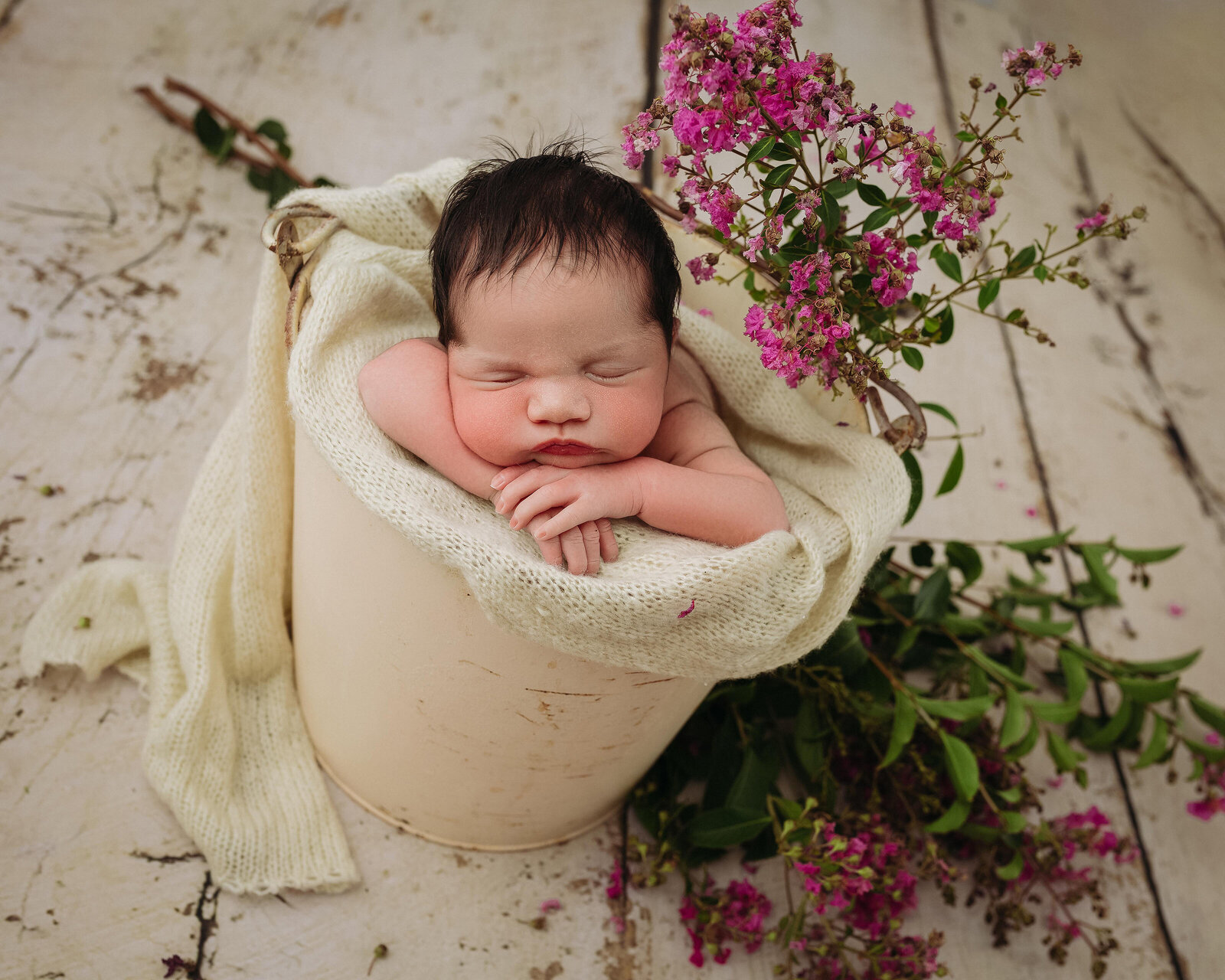 Posed in-studio portrait of newborn baby in bucket with flowers.