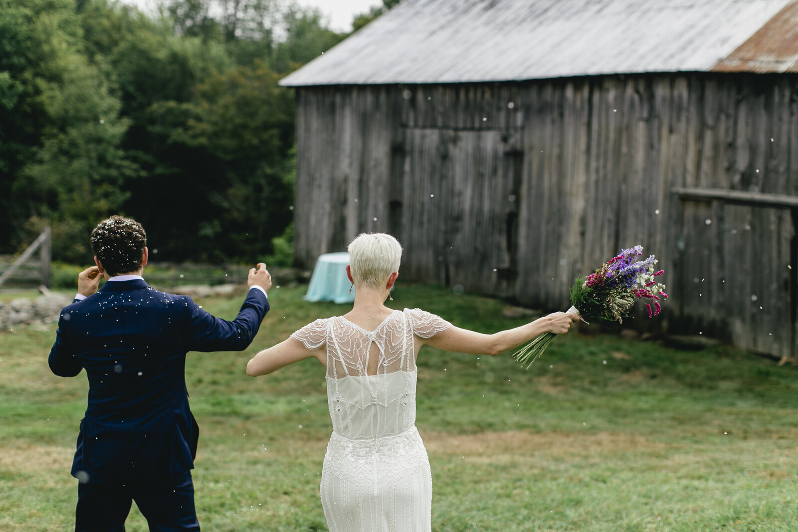 bride and groom celebrating at old barn