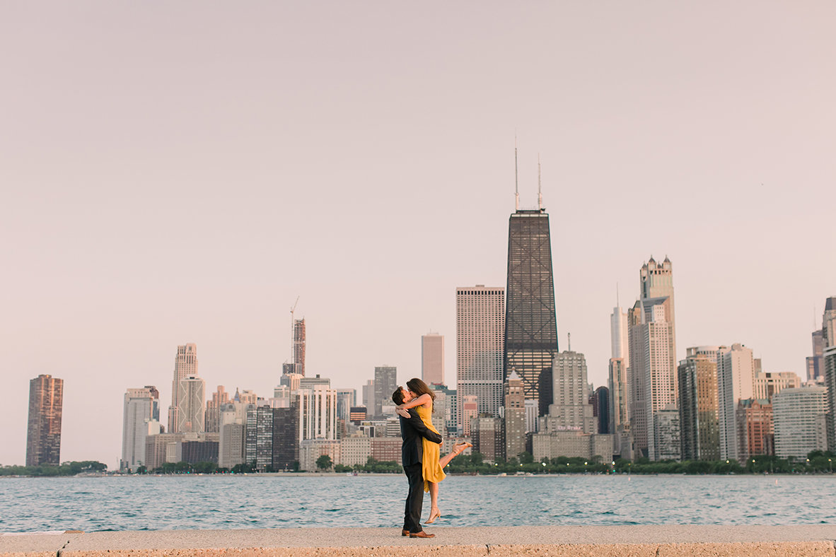 Couple pose in front of the Chicago skyline at North Avenue Beach for an engagement photo.
