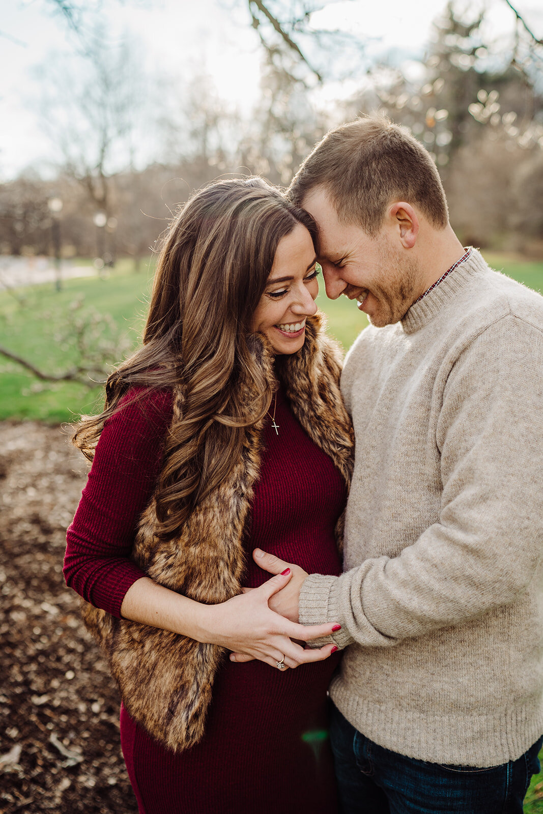 pregnant couple laughs together during winter maternity session