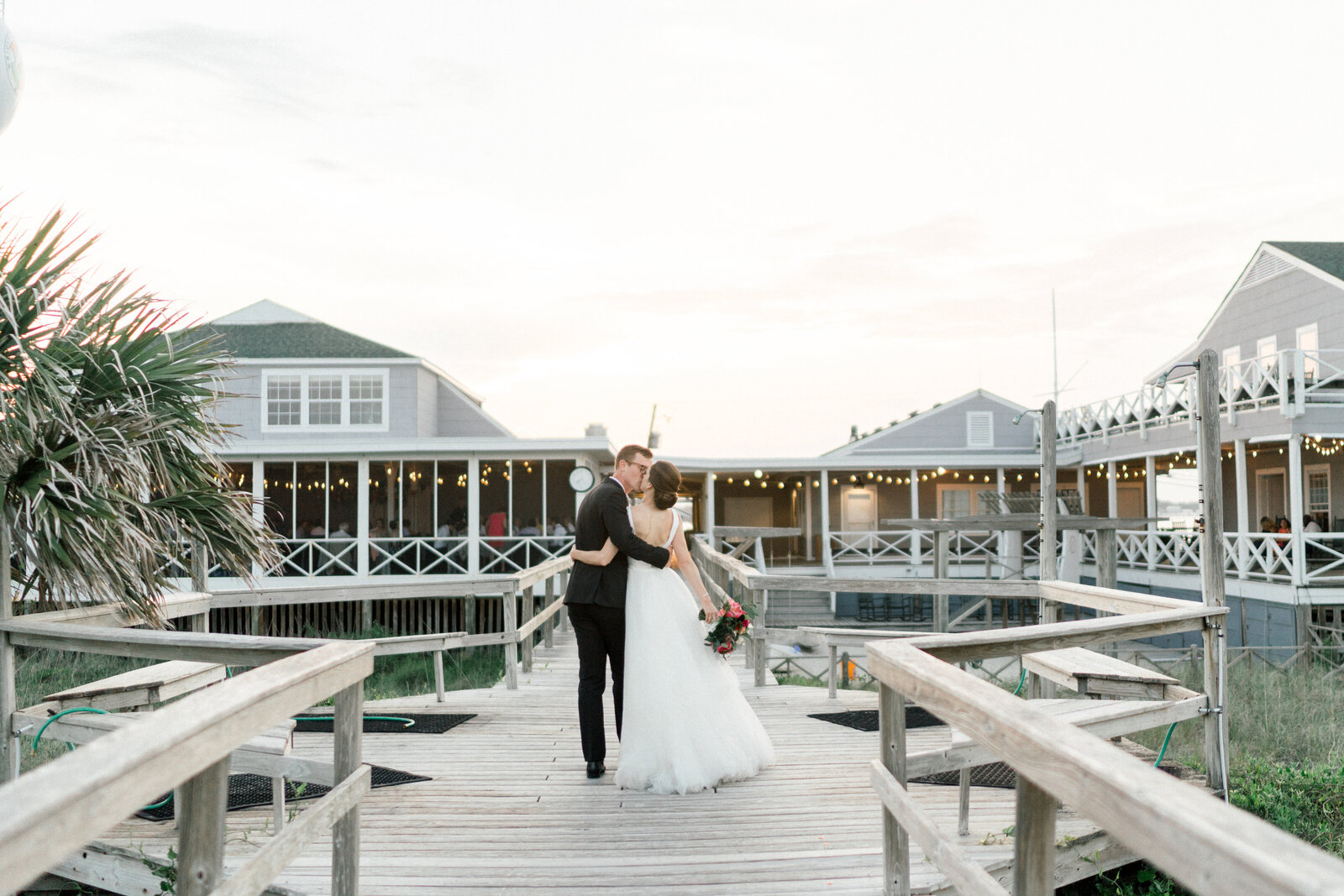 couple kissing and  walking from the beach into their reception at the Carolina Yacht Club