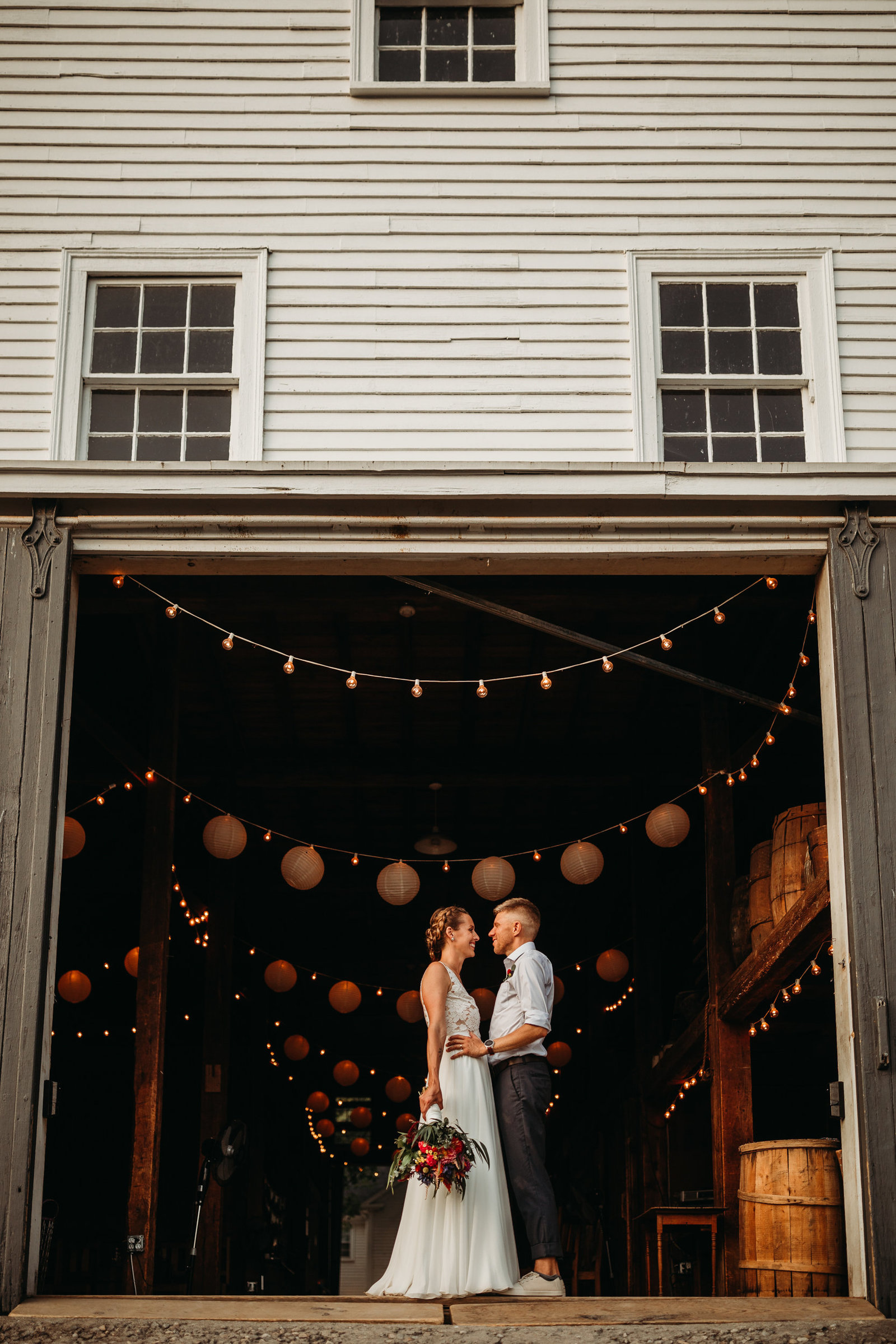 bride and groom stand in doorway of barn with twinkle lights in mass