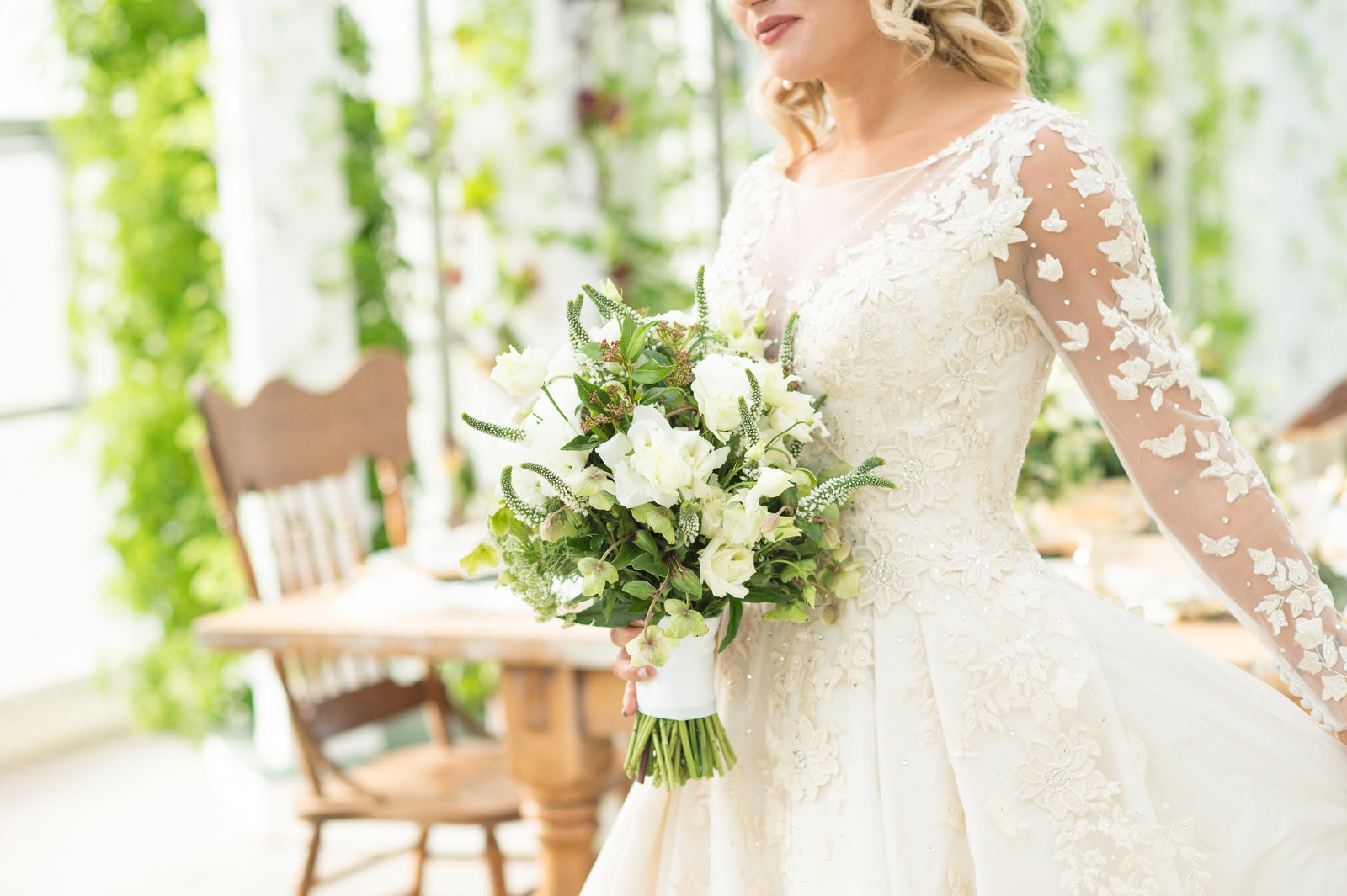 Beautiful bride in room of greenery holding bouquet