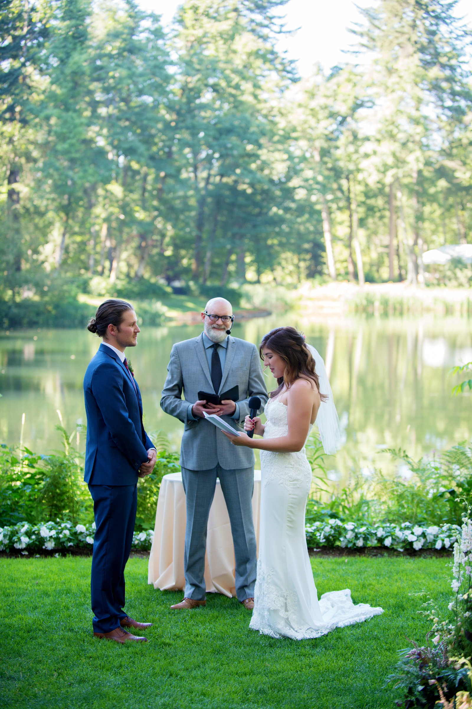 bride and groom read their vows during the ceremony with bridal veil lake in the background