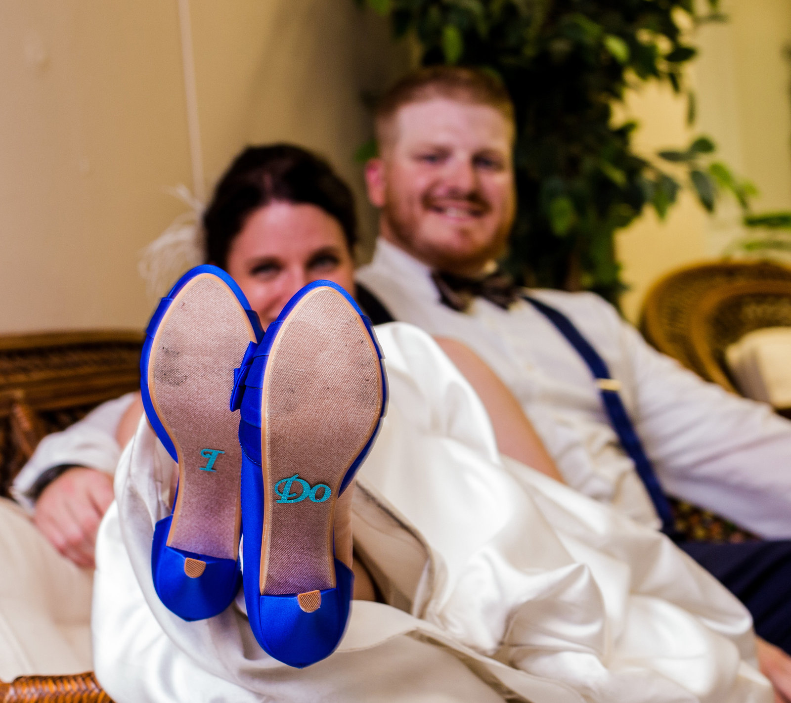 Bride and groom relax on a sofa during their Masonic Temple wedding reception in Erie, PA