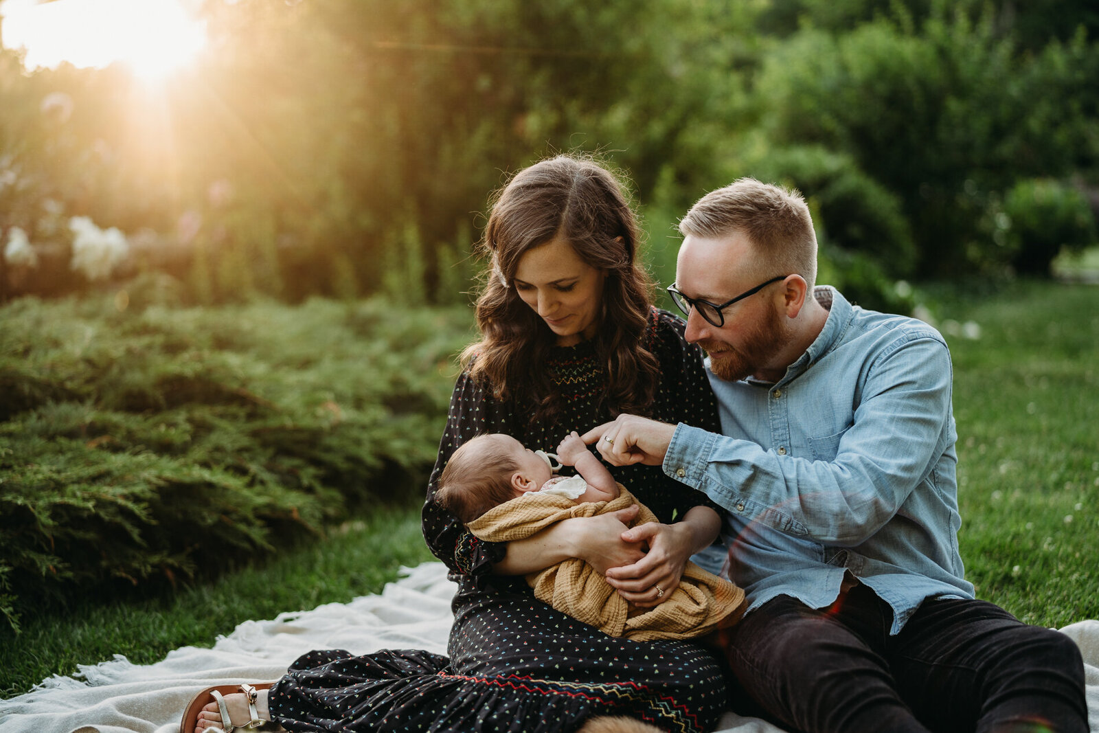 couple sits in park at sunset with newborn baby