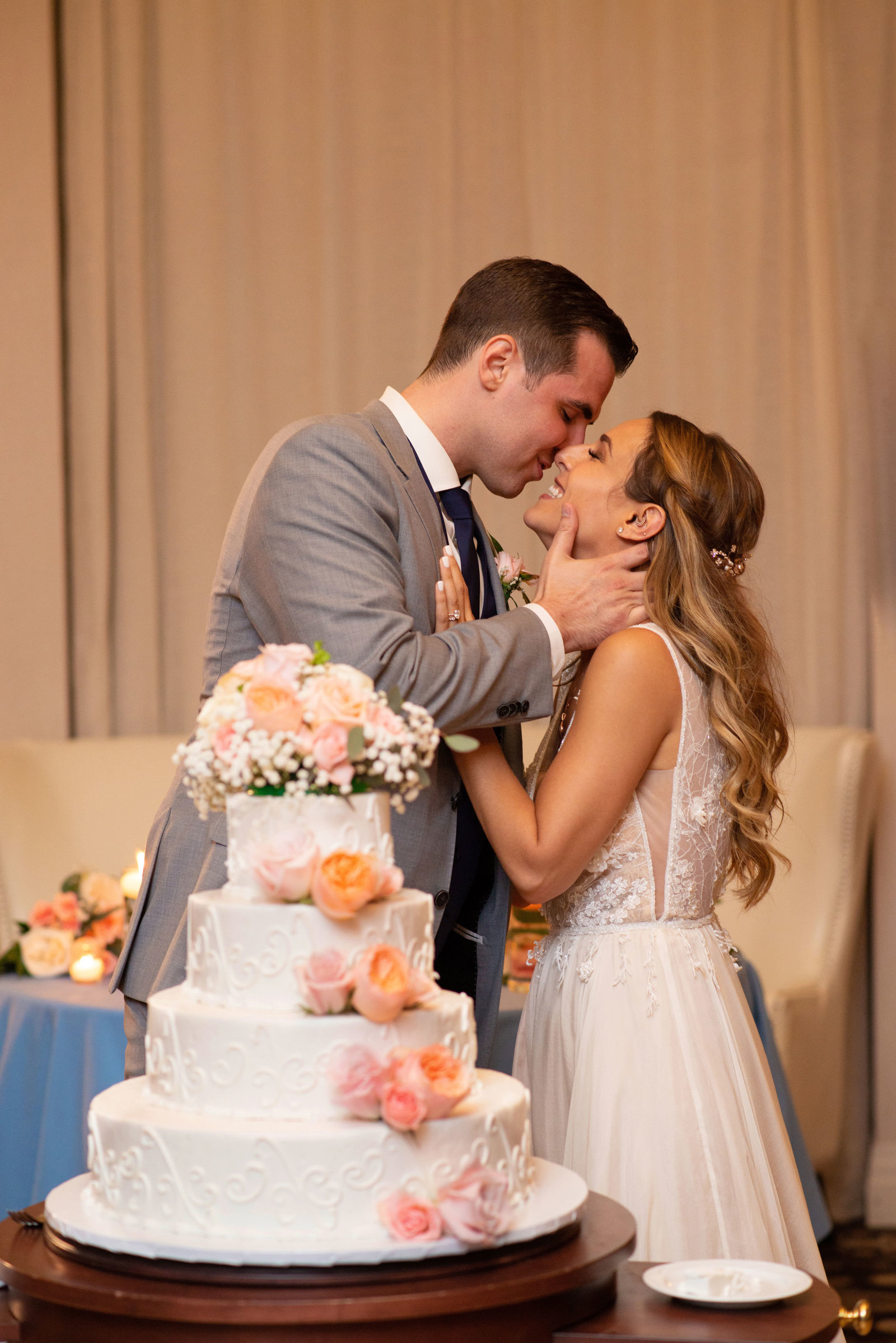 Bride and groom kissing in front of cake at Atlantis Banquet and Events