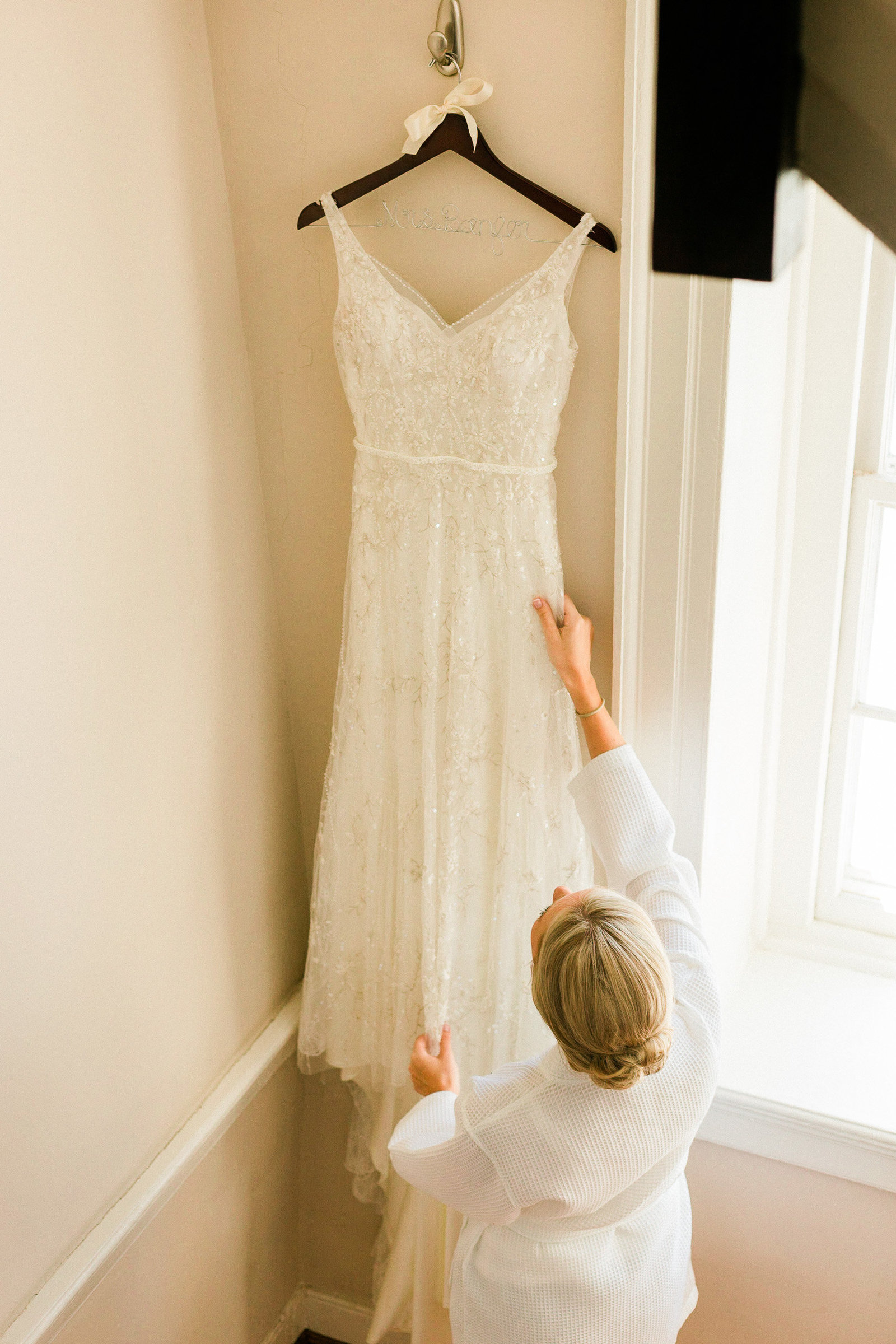 Bride look at her wedding dress hanging up