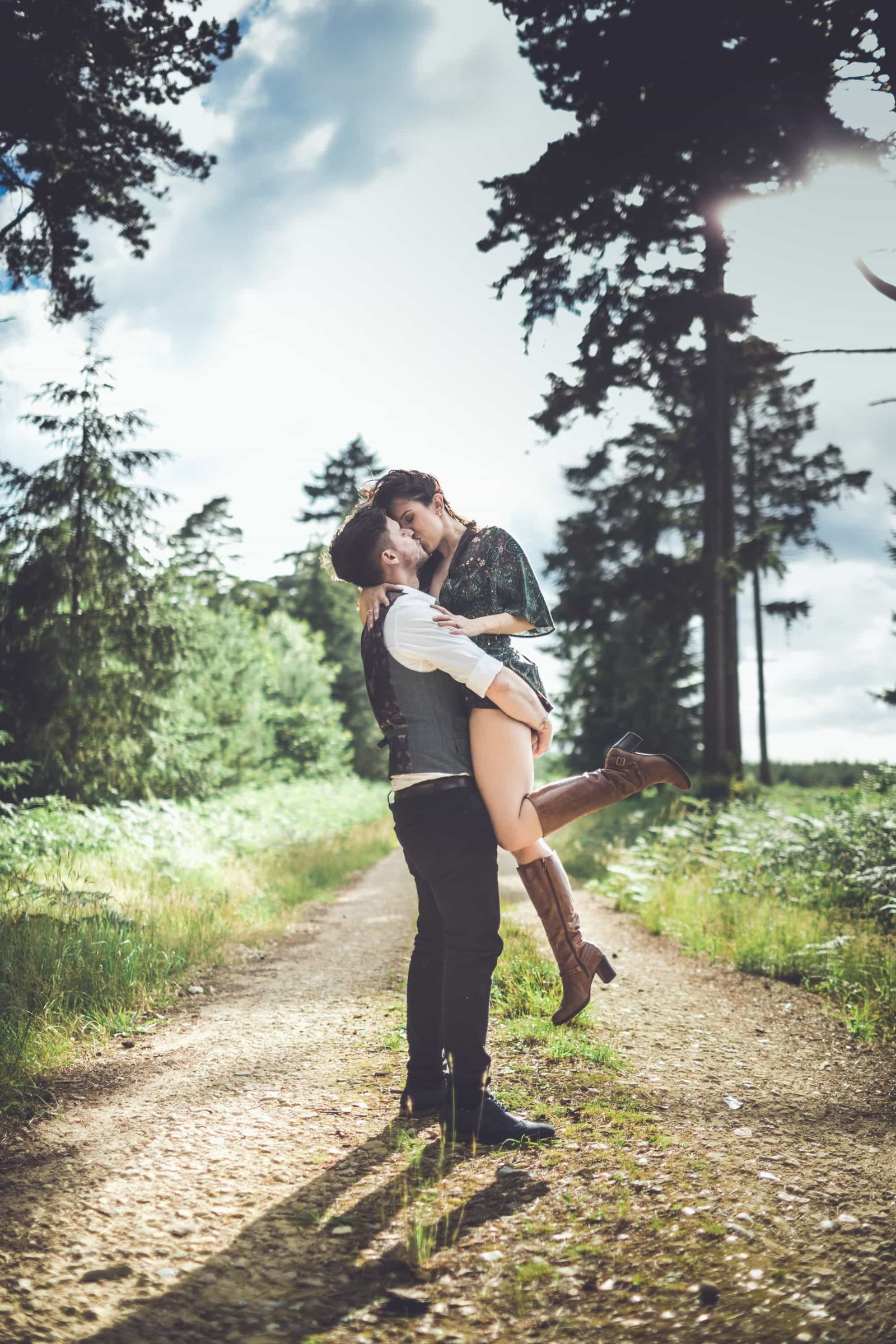 An engaged man lifts his future bride into the air on a gravel path at Bacton forest in Norfolk and they kiss.