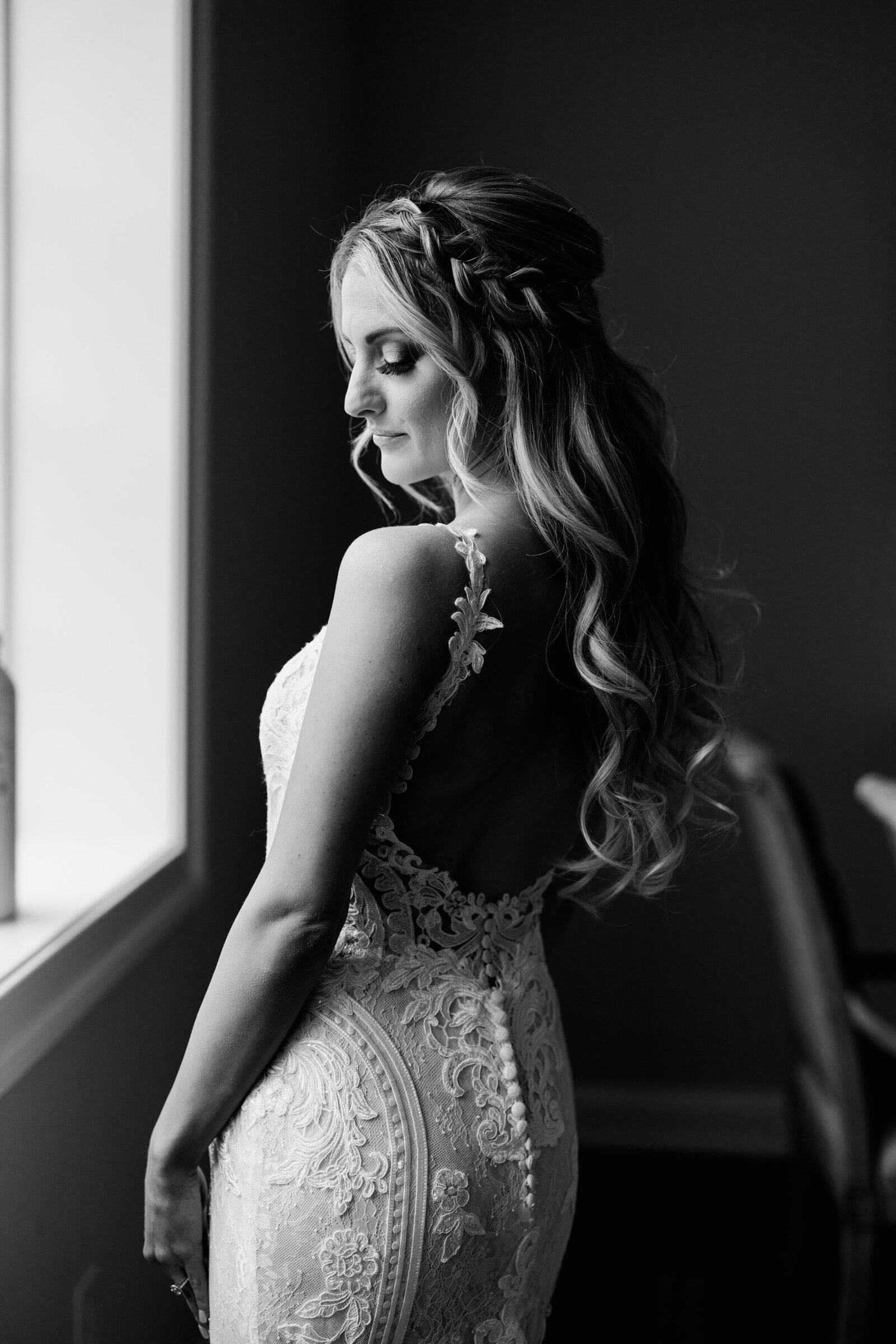 black and white image of bride lace dress at window
