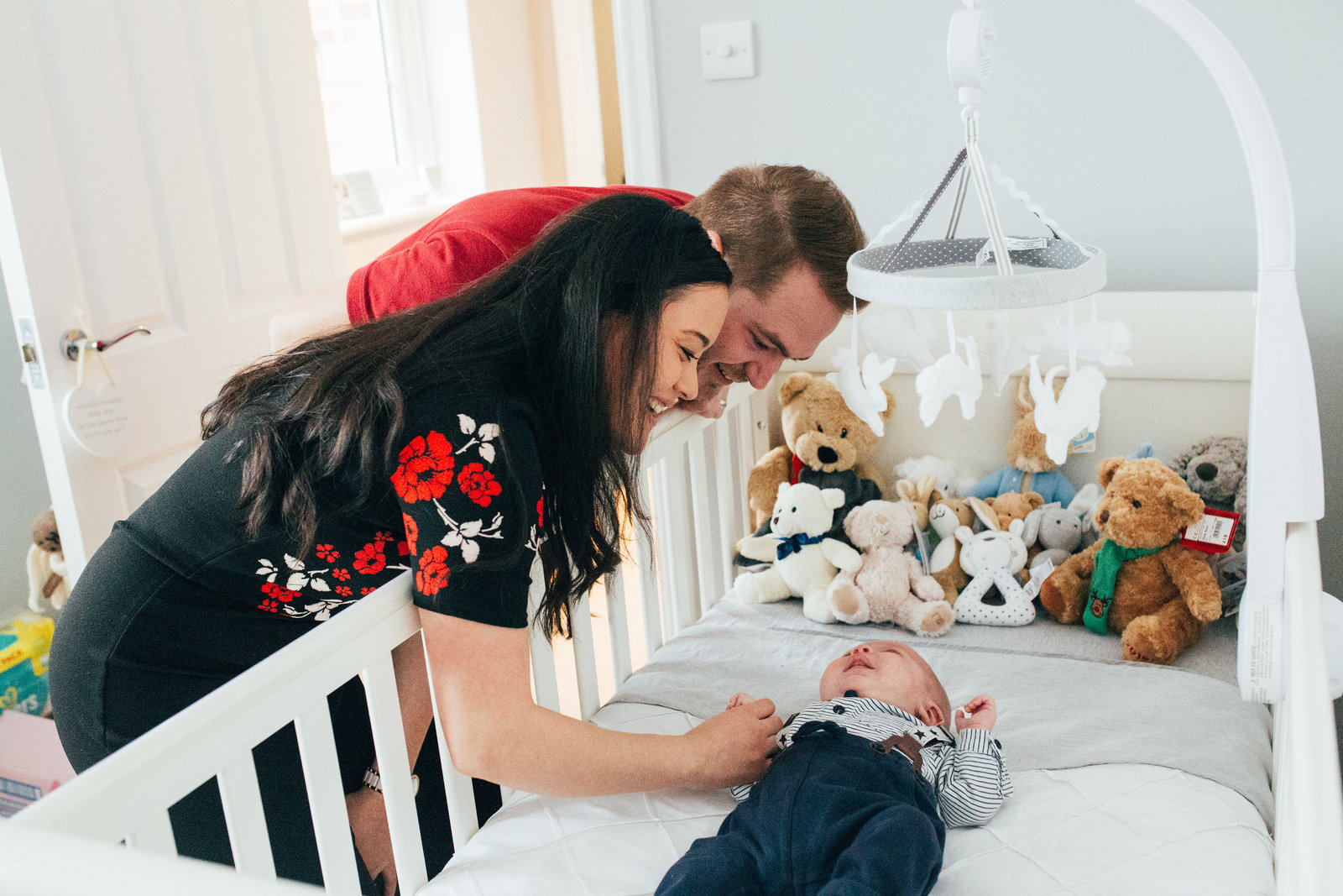 Smiling natural new parents leaning over cot at their newborn baby