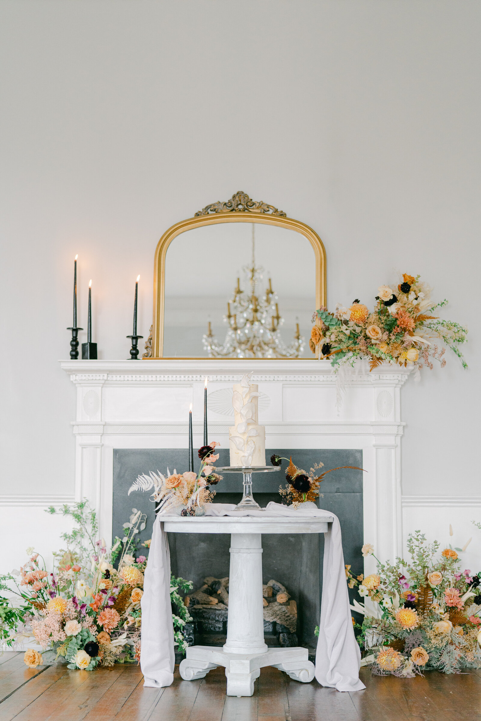 wedding cake on a stand in front of mantel with floral arrangements all around