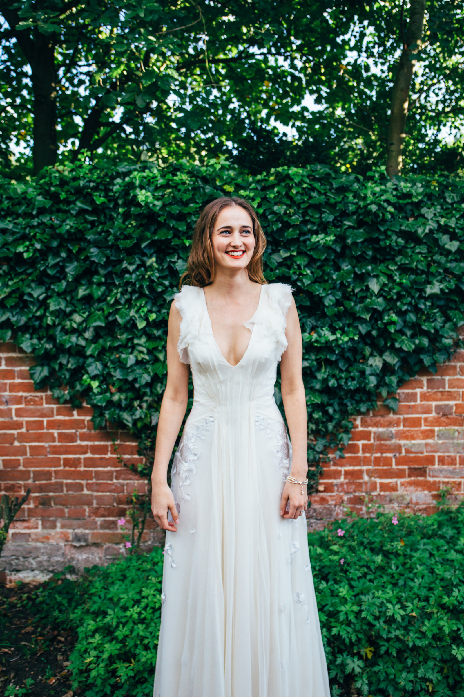 Beautiful relaxed smiling bride outside on a  sunny day after her wedding at Blackthorpe Barn, Suffolk