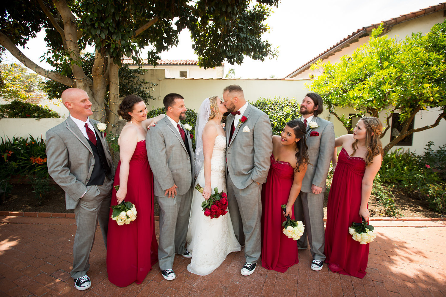 bridal party with red dresses and white flowers