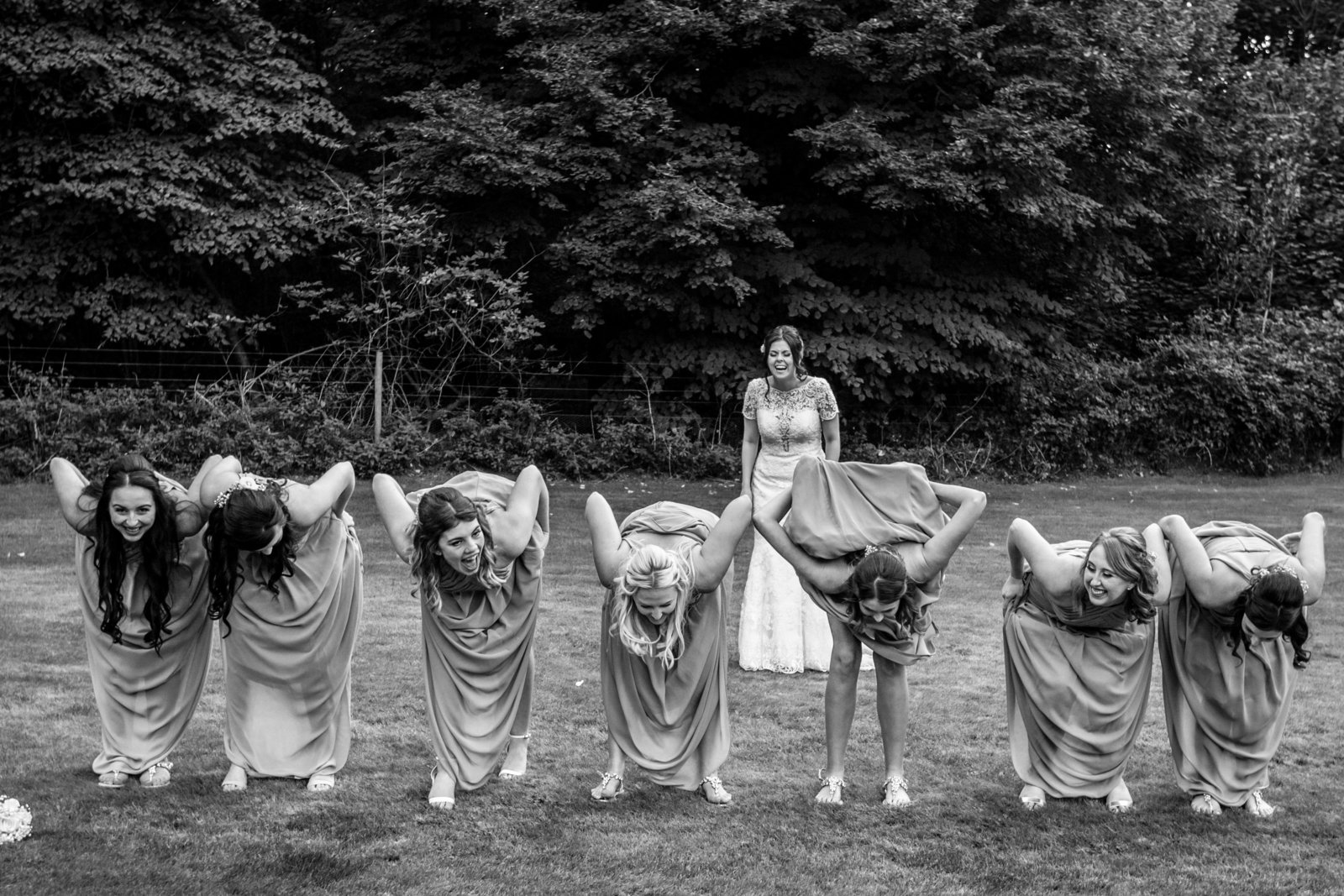 Bridesmaids stand in a line to bend over at flash their pants at the Bride who is standing behind them and laughing at a venue in Norfolk.