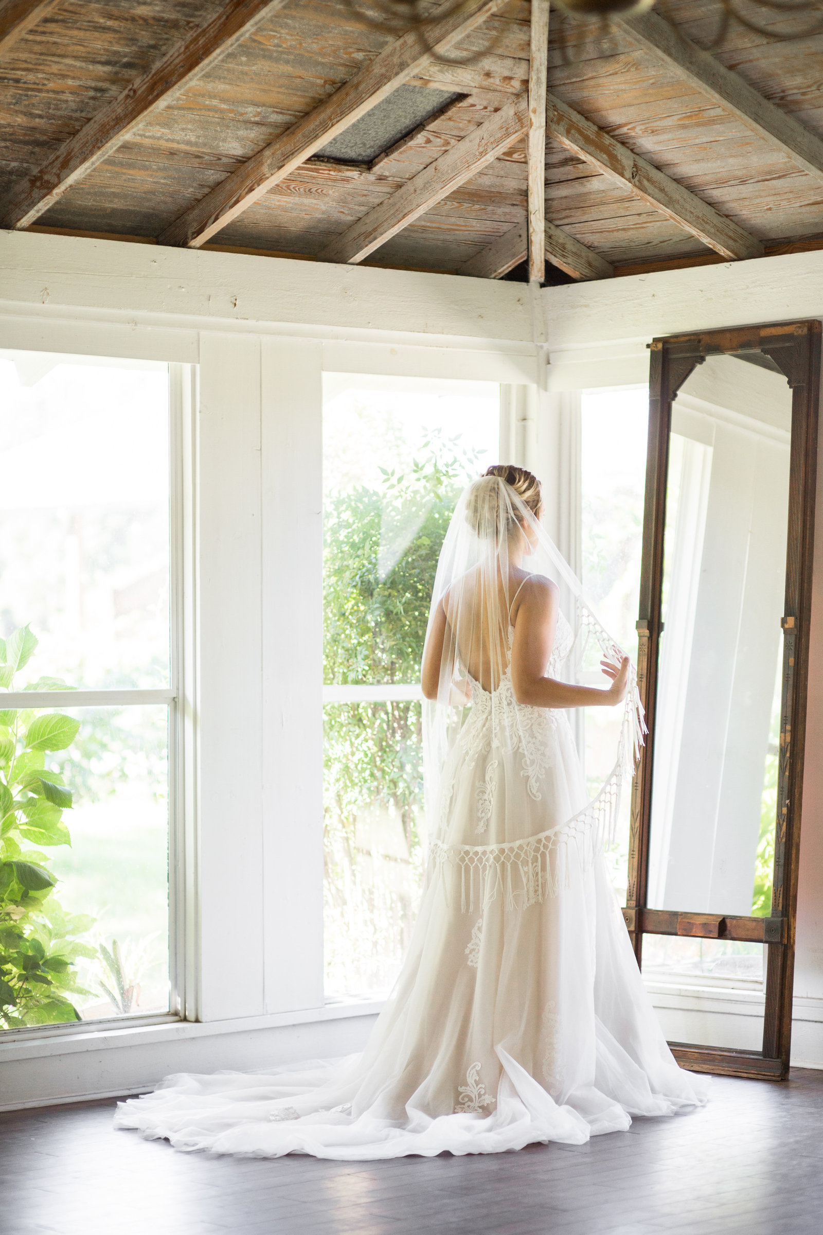 bride getting ready in front of mirror with windows all around at woodlawn plantation in guyton