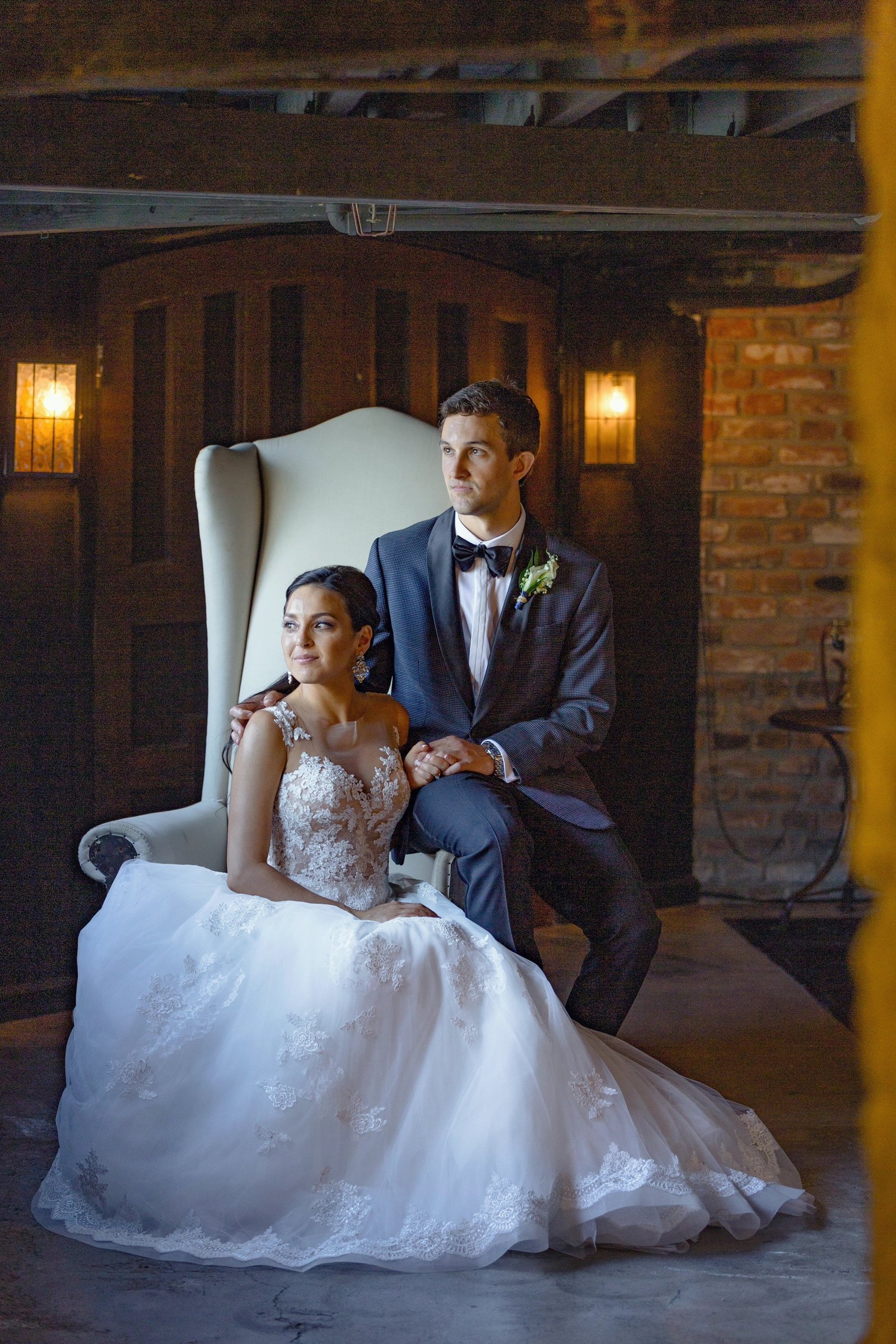 regal bride and groom on chair portraits in the newhall mansion tavern