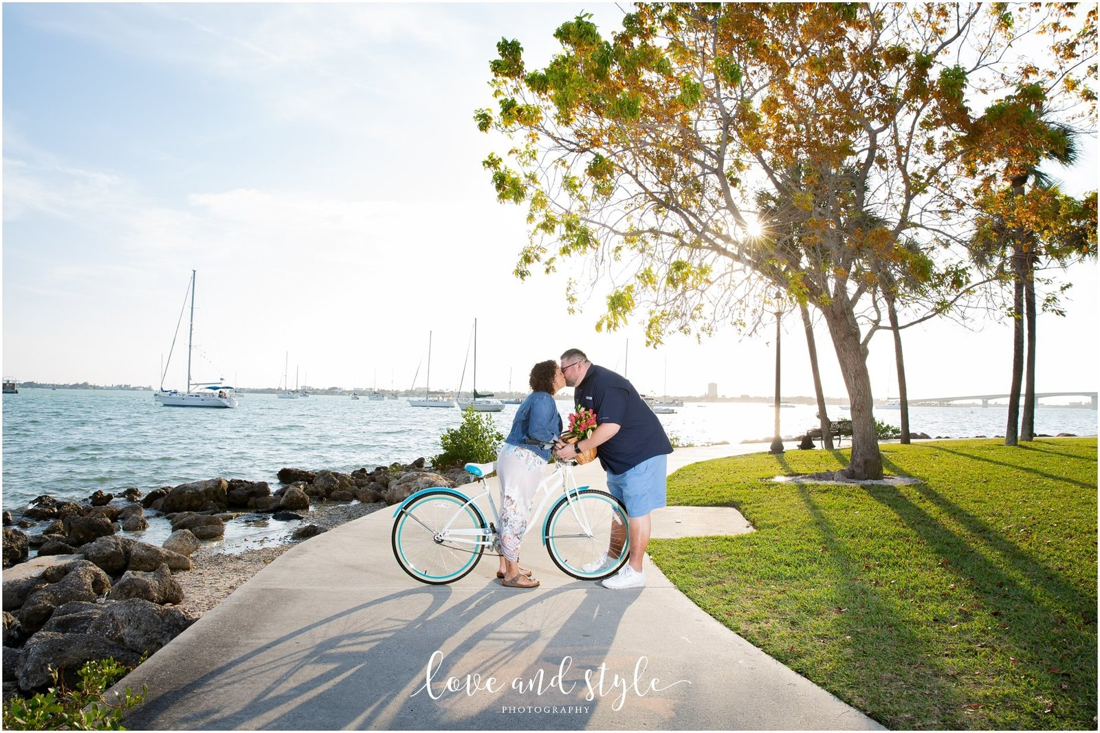 Engagement Photography at Bayfront Park, Sarasota kissing with a bike