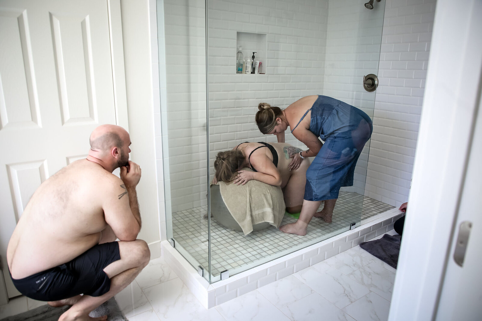 Woman laboring in shower with her doula