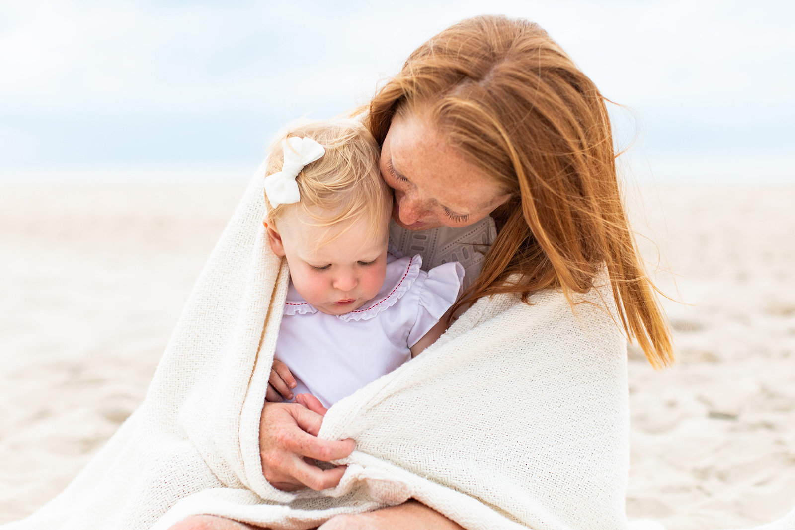 mother sitting on beach with her toddler daughter