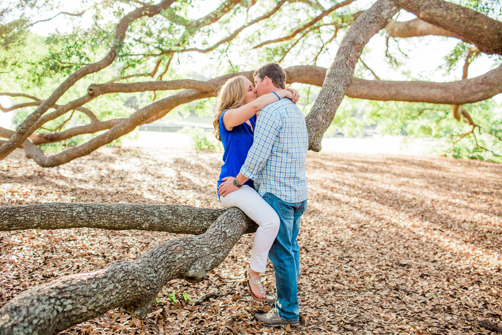 Engaged couple cuddle underneath an oak tree, Hampton Park, Charleston, South Carolina