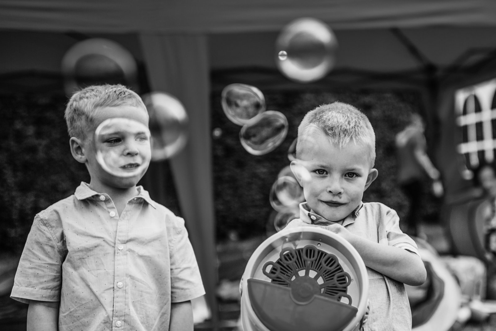 Two young wedding guests point a bubble machine at the camera at a Norfolk wedding venue.