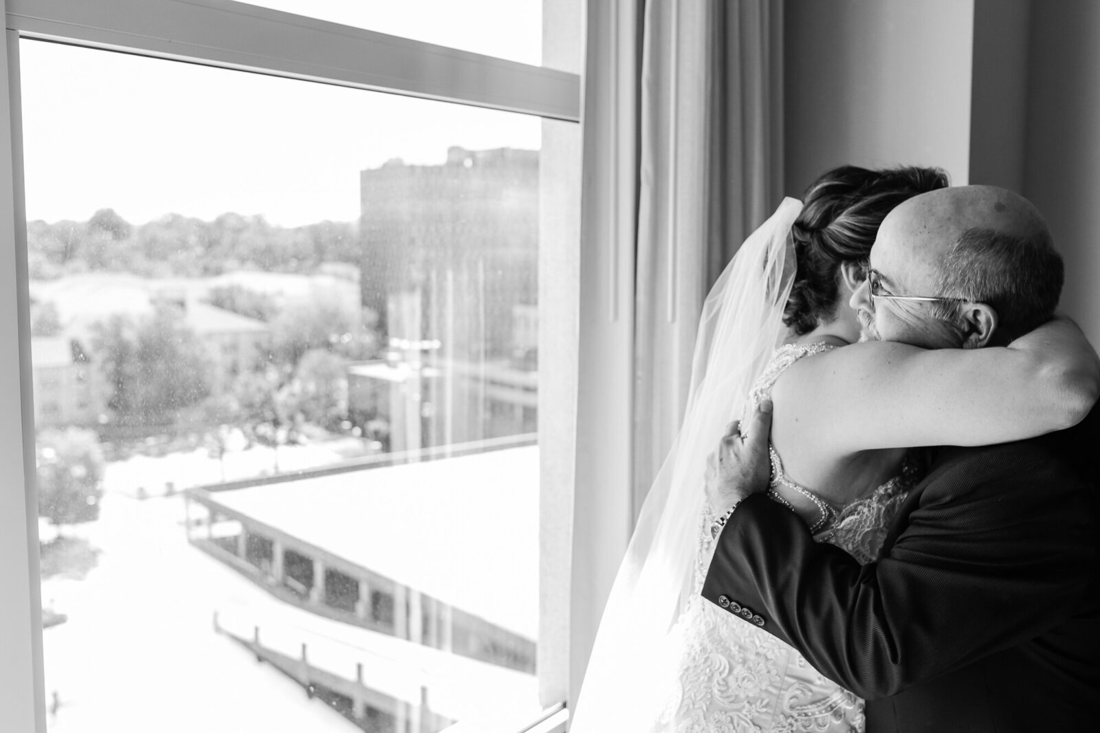 Black and white candid photo of an emotional first look between a bride and her father