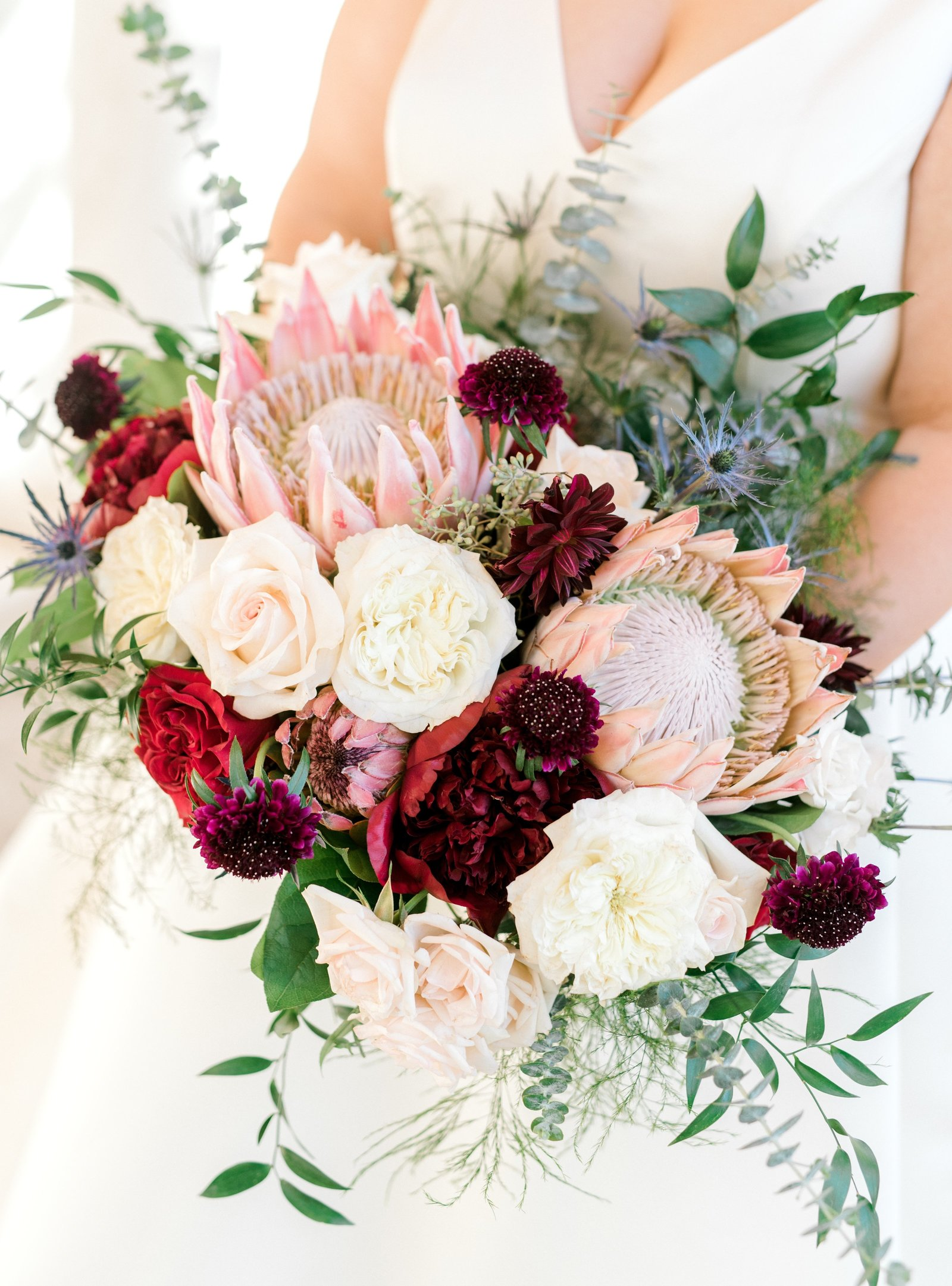 Bridal bouquet with King protea and burgundy and blush roses