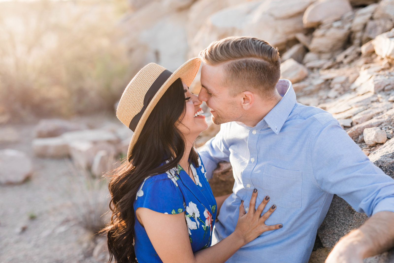 Engaged couple smiling at each other leaning against a rock in the desert