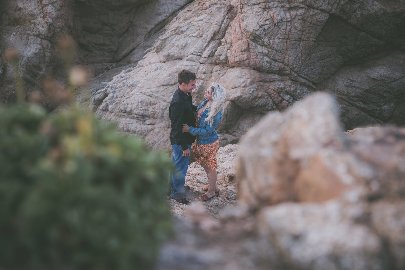 Couple framed between bushes and rock in Big Sur.