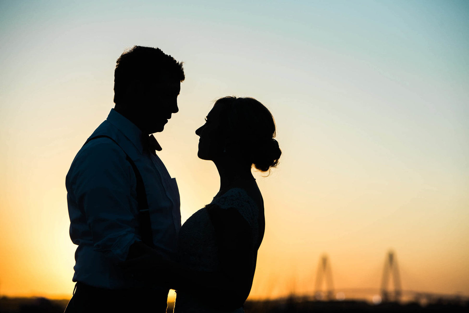 Bride and groom stand near Ravenel Bridge at sunset, Alhambra Hall, Mt Pleasant, South Carolina. Kate Timbers Photography.