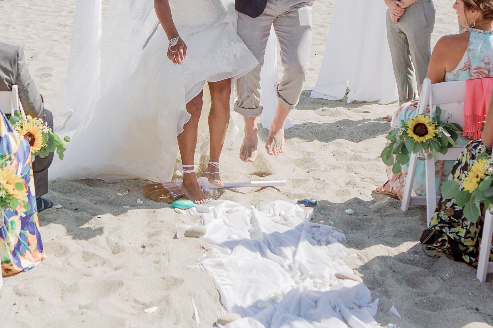 Wedding couple jumping over the broom at the beach by San Luis Obispo wedding photographer Renoda Campbell Photography