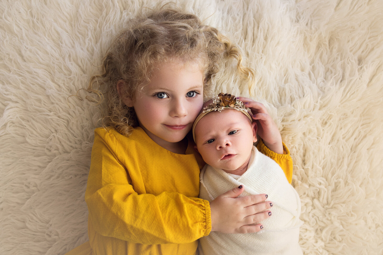 In-studio portrait of girl holding newborn baby sister