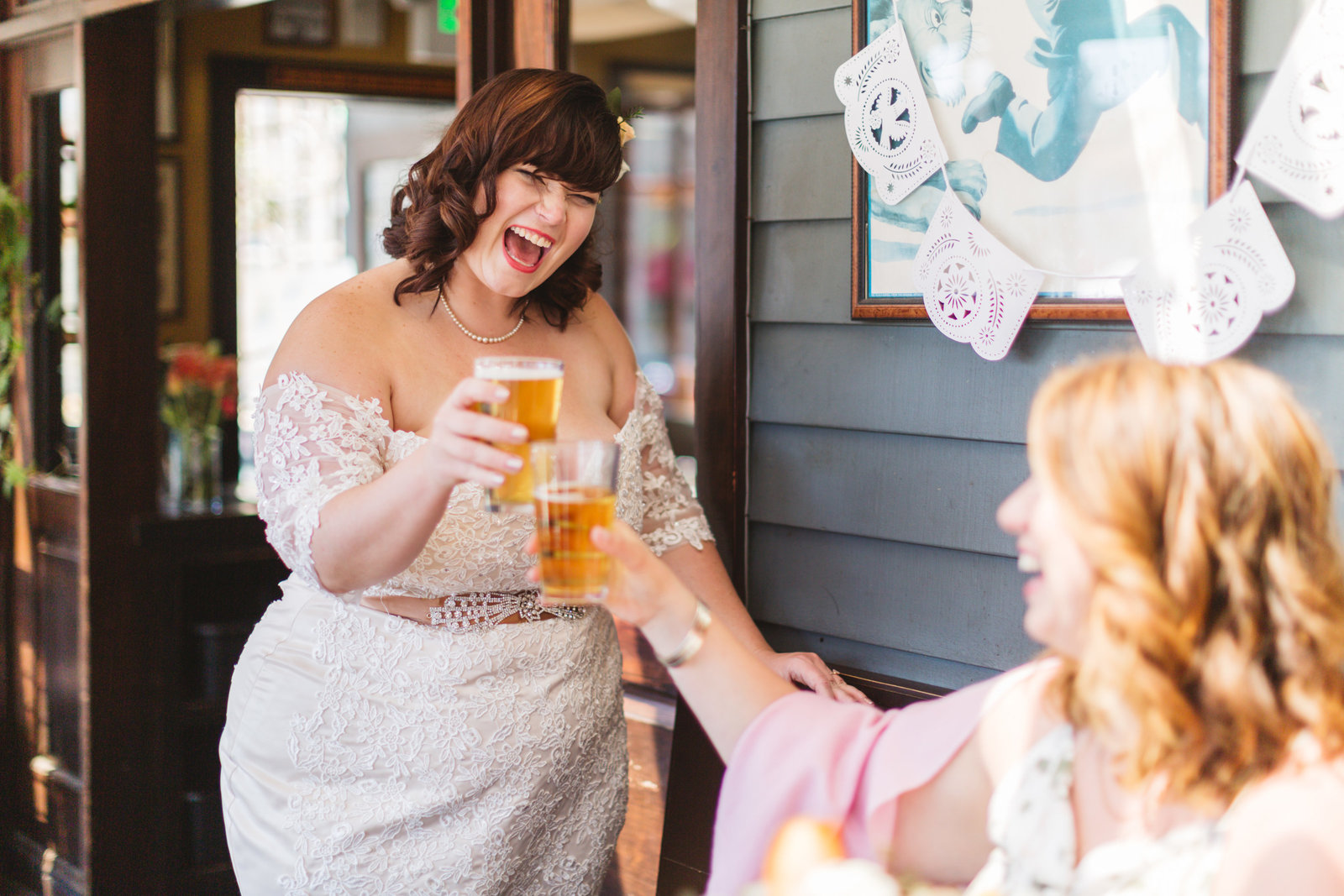bride cheersing her friend at cato's ale house wedding in Oakland