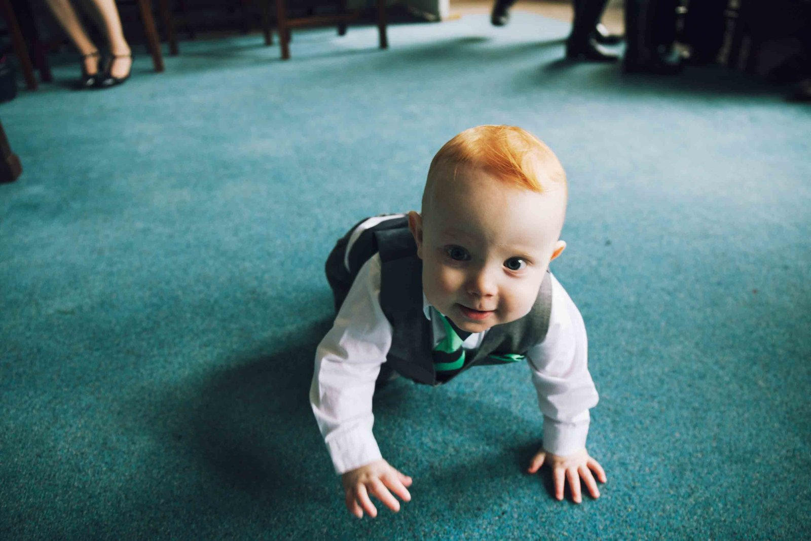 Photograph of surprised toddler boy crawling at home in Suffolk